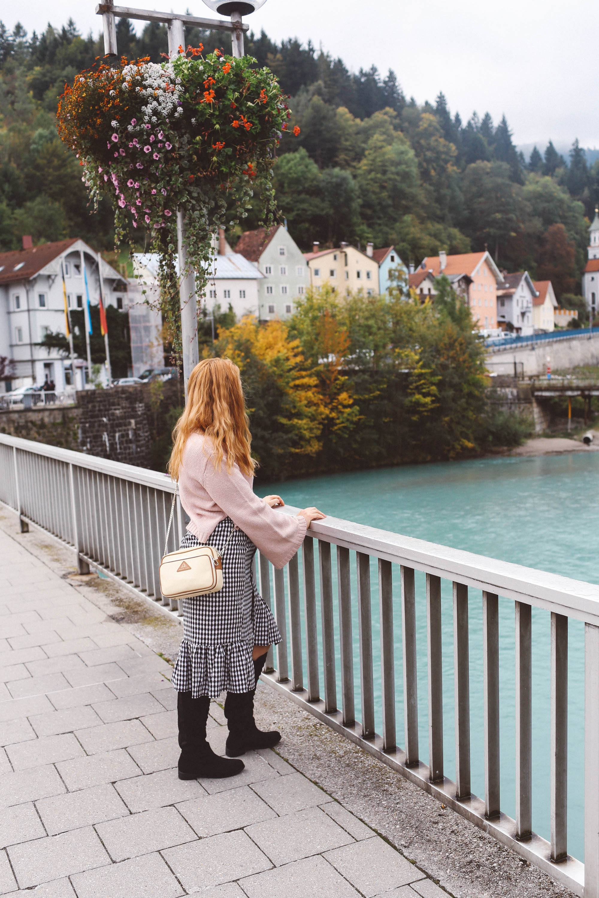 Füssen, Germany pink sweater gingham skirt river water houses