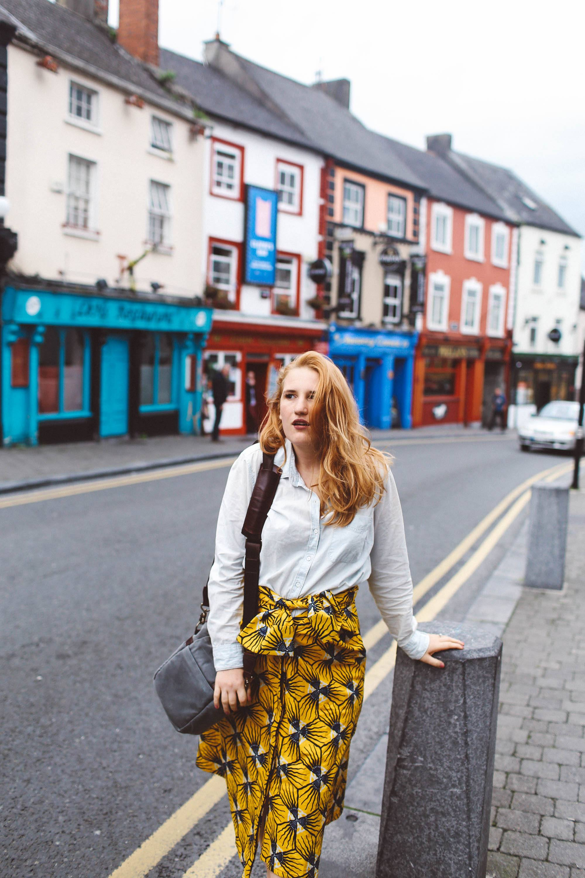 kilkenny ireland woman yellow skirt ona bag