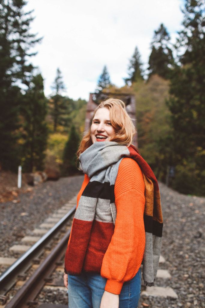 woman train tracks red sweater scarf fall