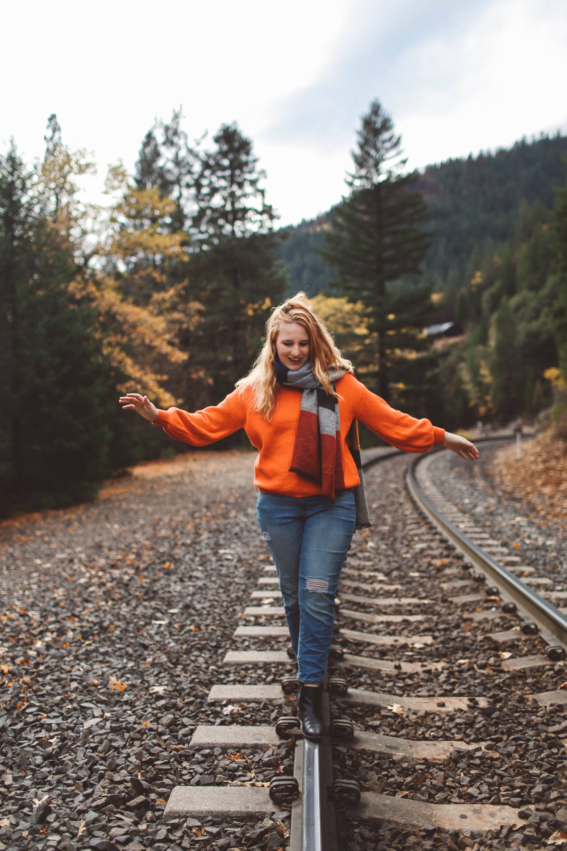woman train tracks red sweater scarf fall