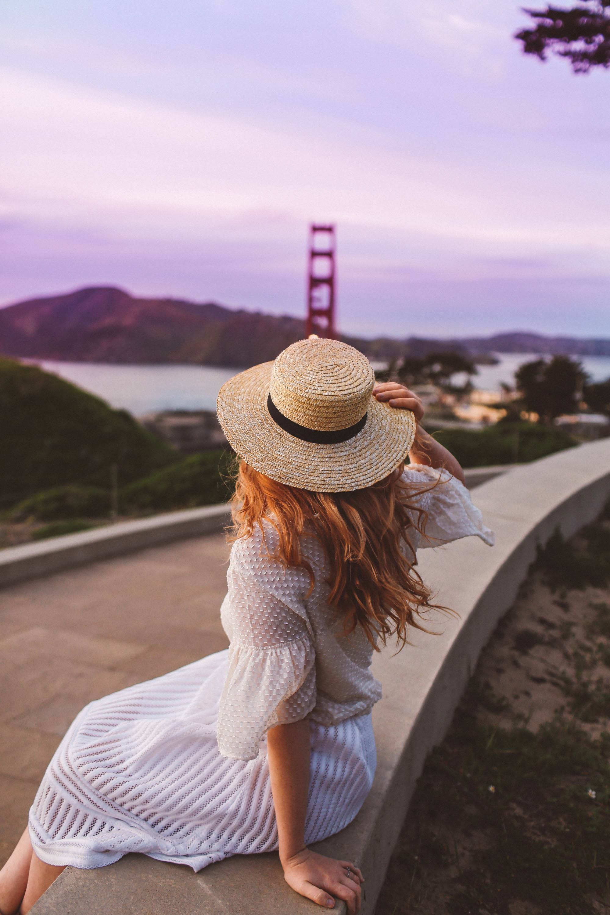 Woman sitting looking at golden gate bridge from afar