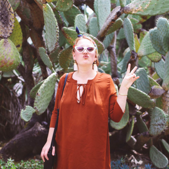 Woman in burnt orange dress in front of cacti