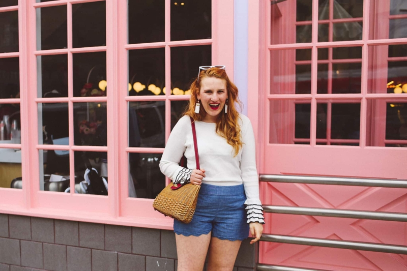 Woman wearing white rimmed sunglasses a white sweater and scallop shorts