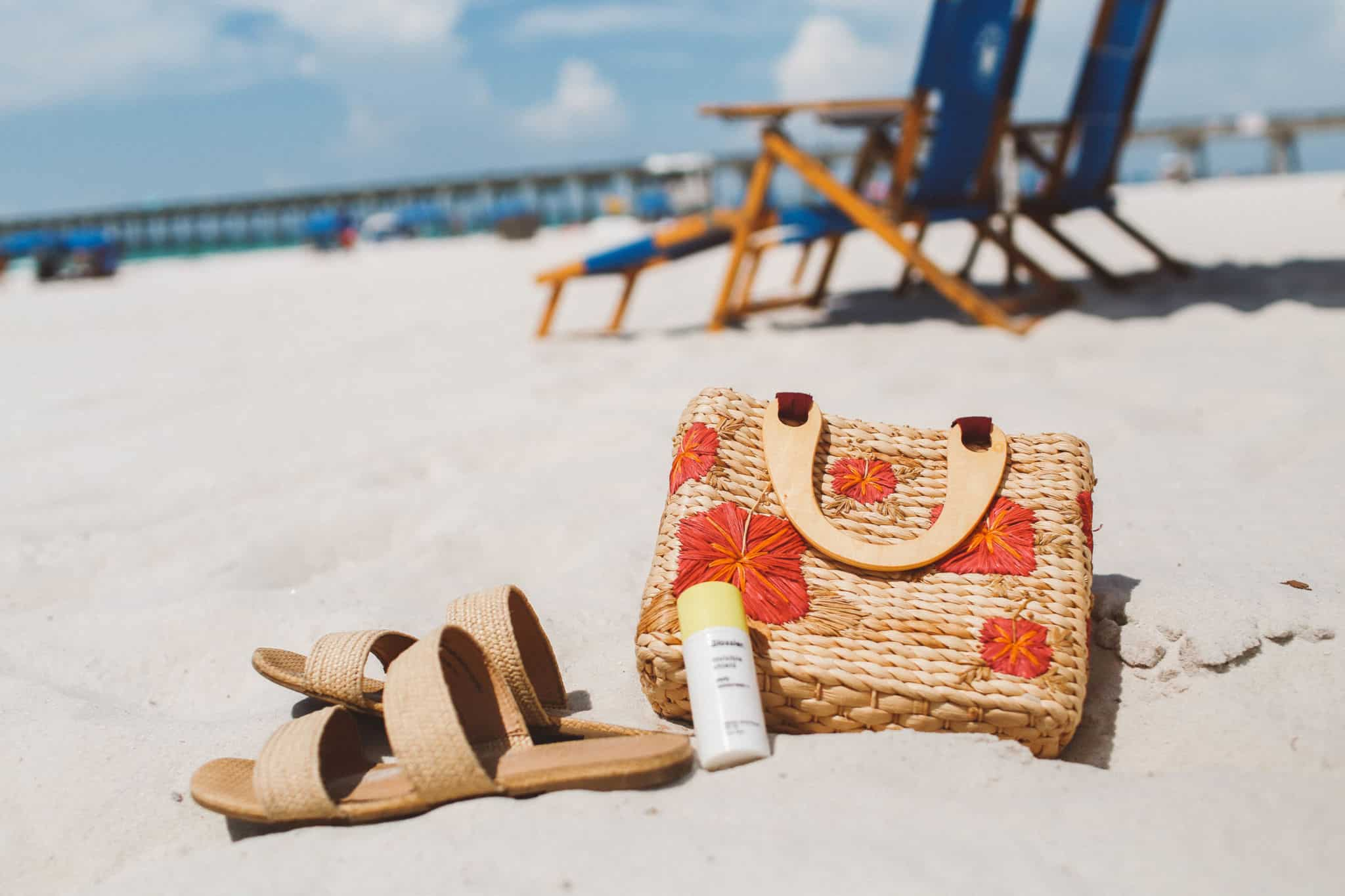 sandals, sunscreen and a floral straw purse on the sand