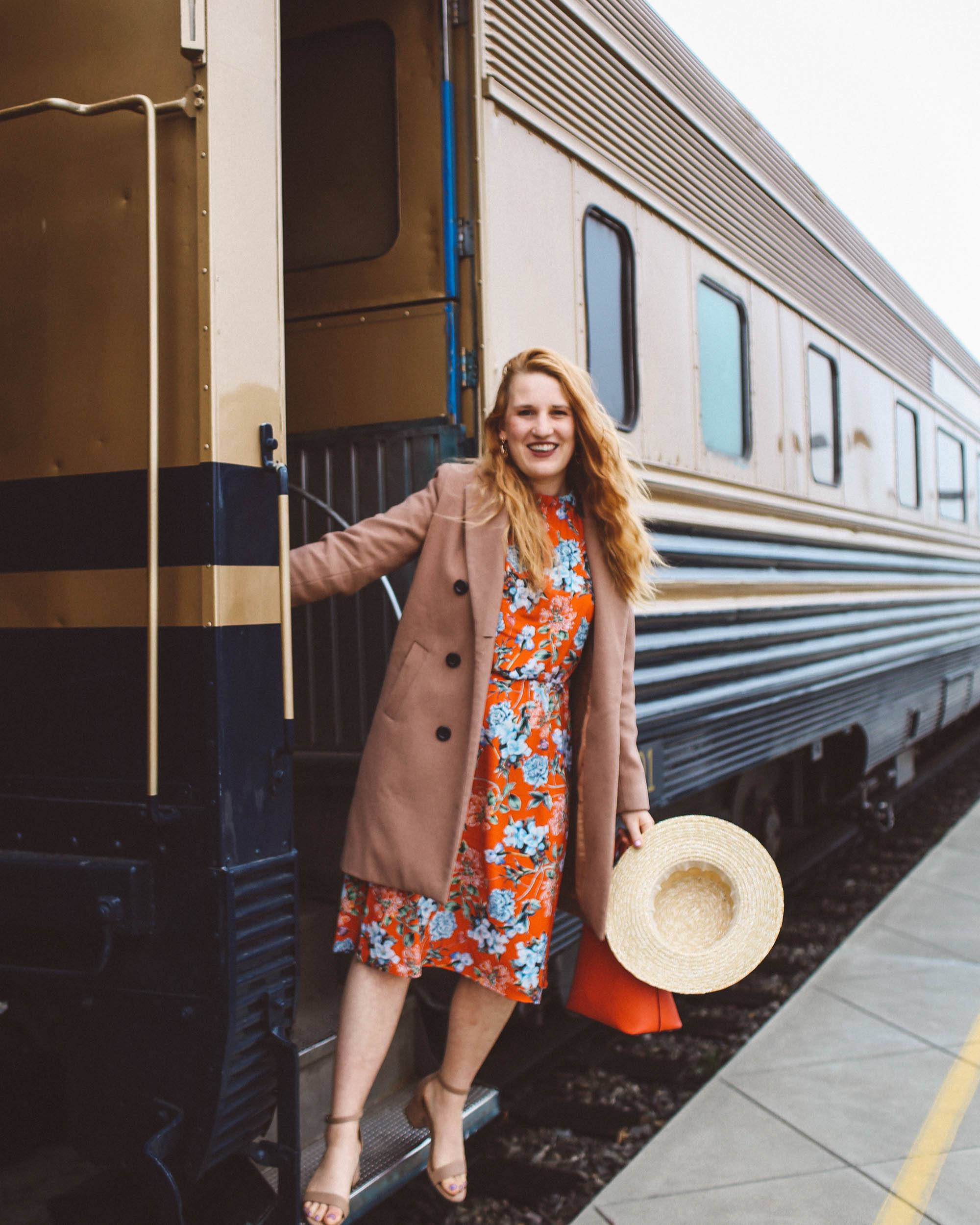 Wiman in floral dress hanging off of Napa Valley Wine Train