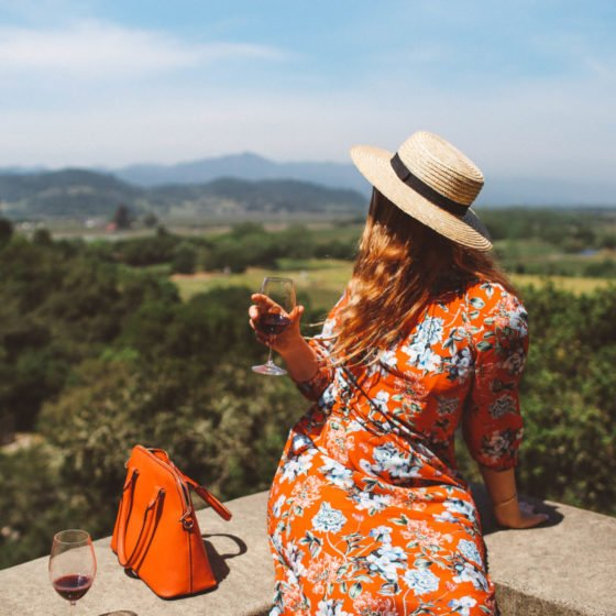 Woman in red floral dress and straw hat drinking wine on a ledge at a Napa Valley Winery