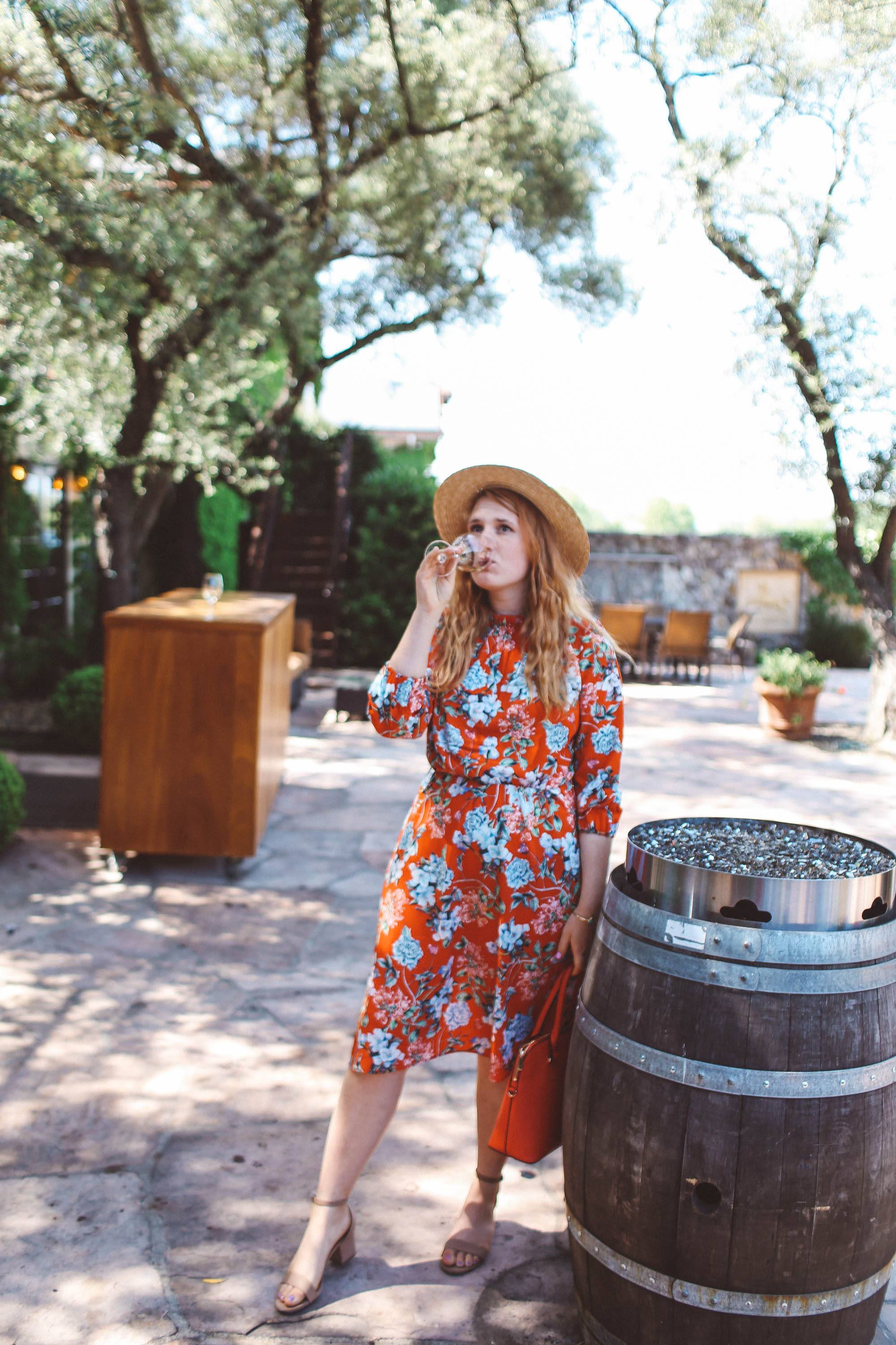 Woman in red floral dress and straw hat drinking wine next to a barrel at Grgich Hills Estate