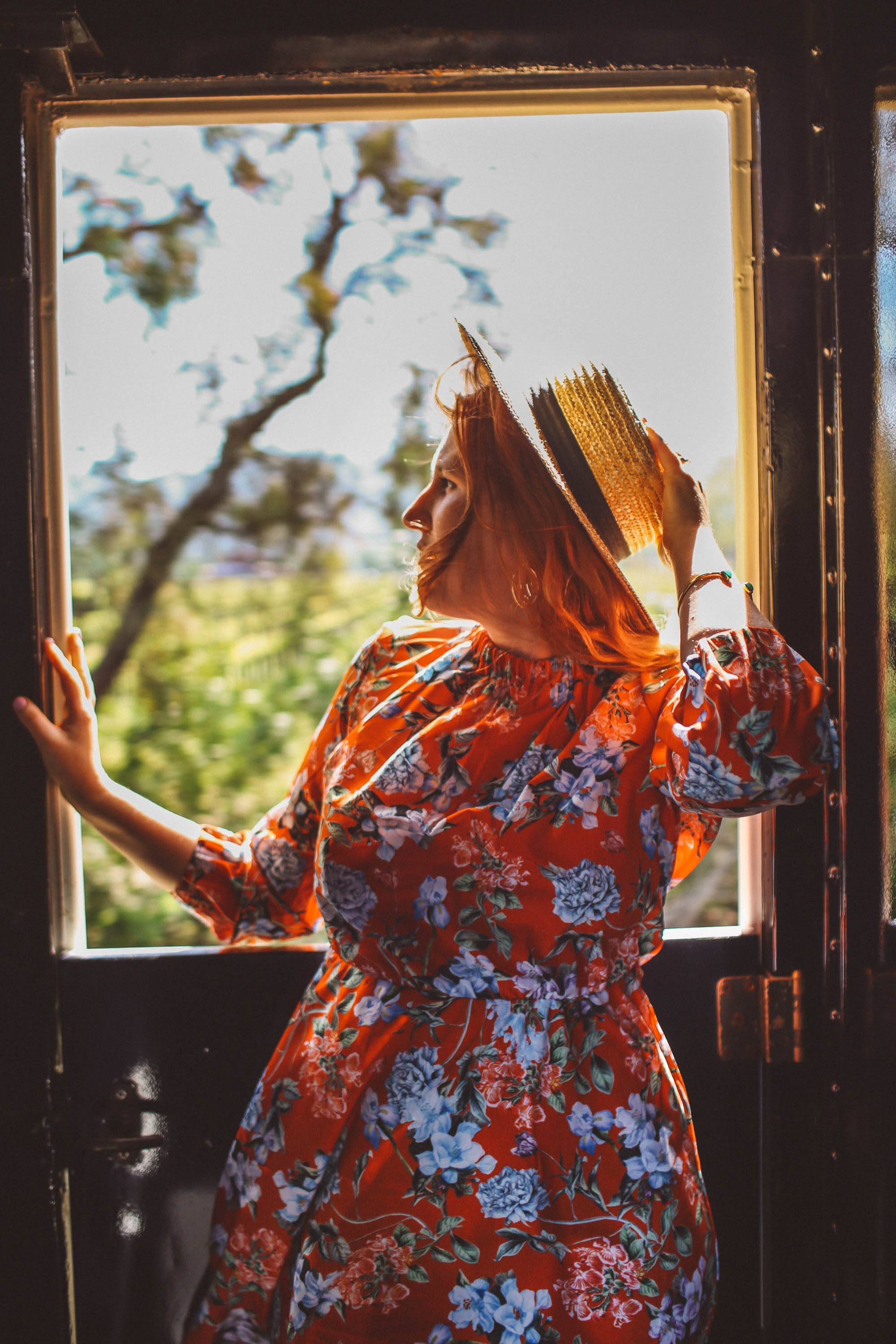 Woman in a red floral dress and a straw hat in front of a window on the Napa Valley Wine Train