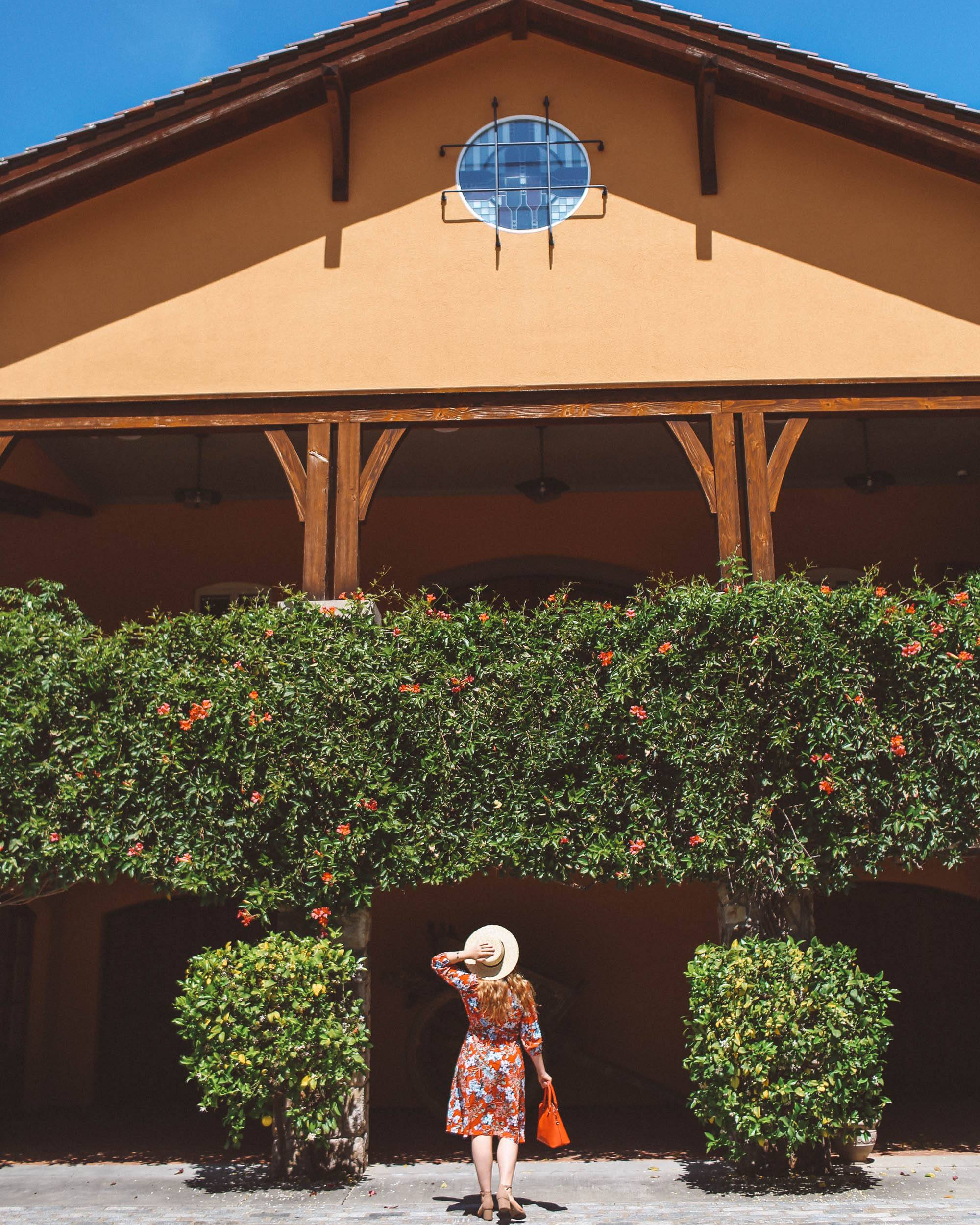 Woman in floral dress and straw hat at a Napa Valley Winery