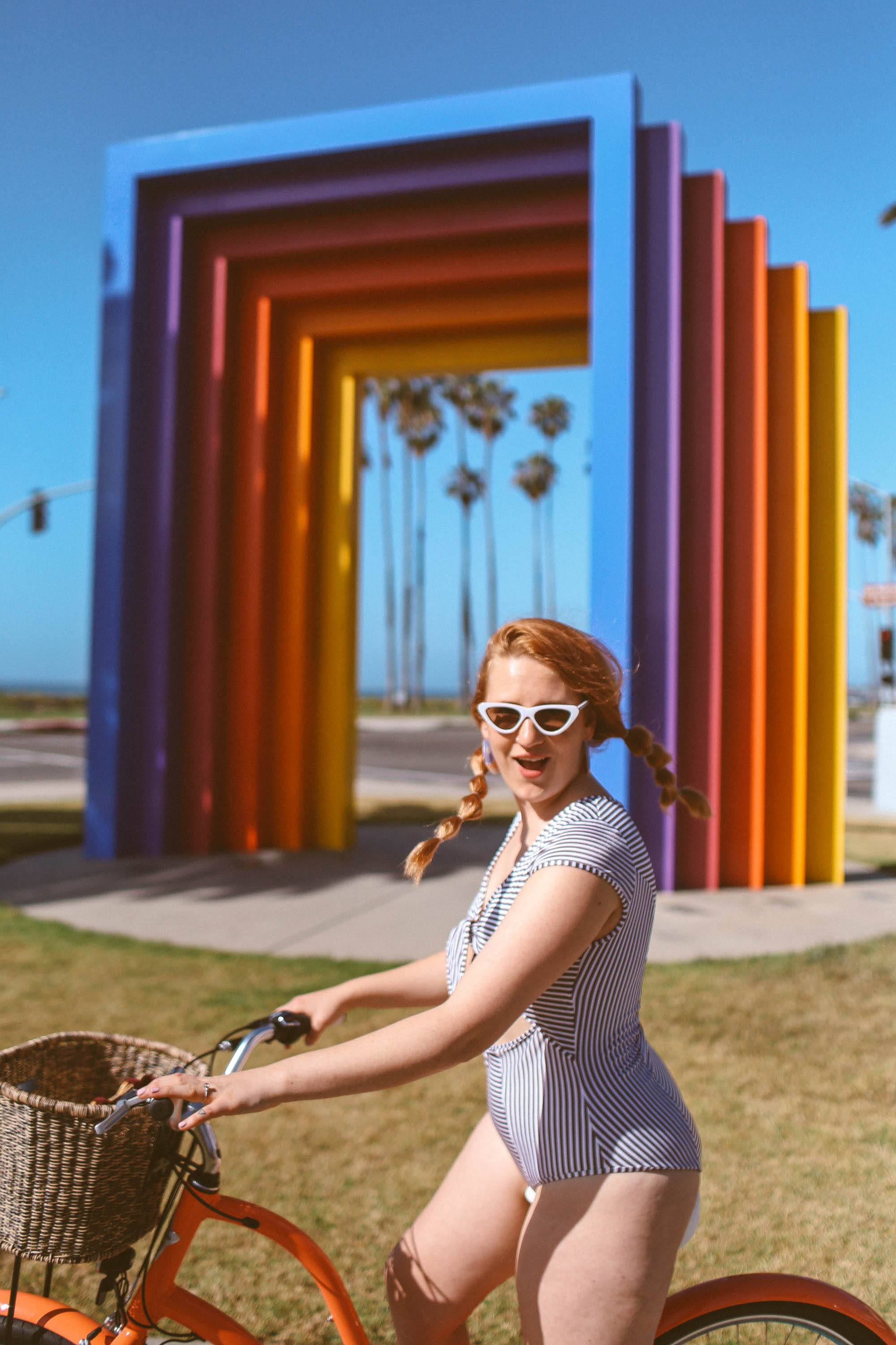Woman in black and white striped front tie swimsuit riding a bike at the chromatic gate in Santa Barbara