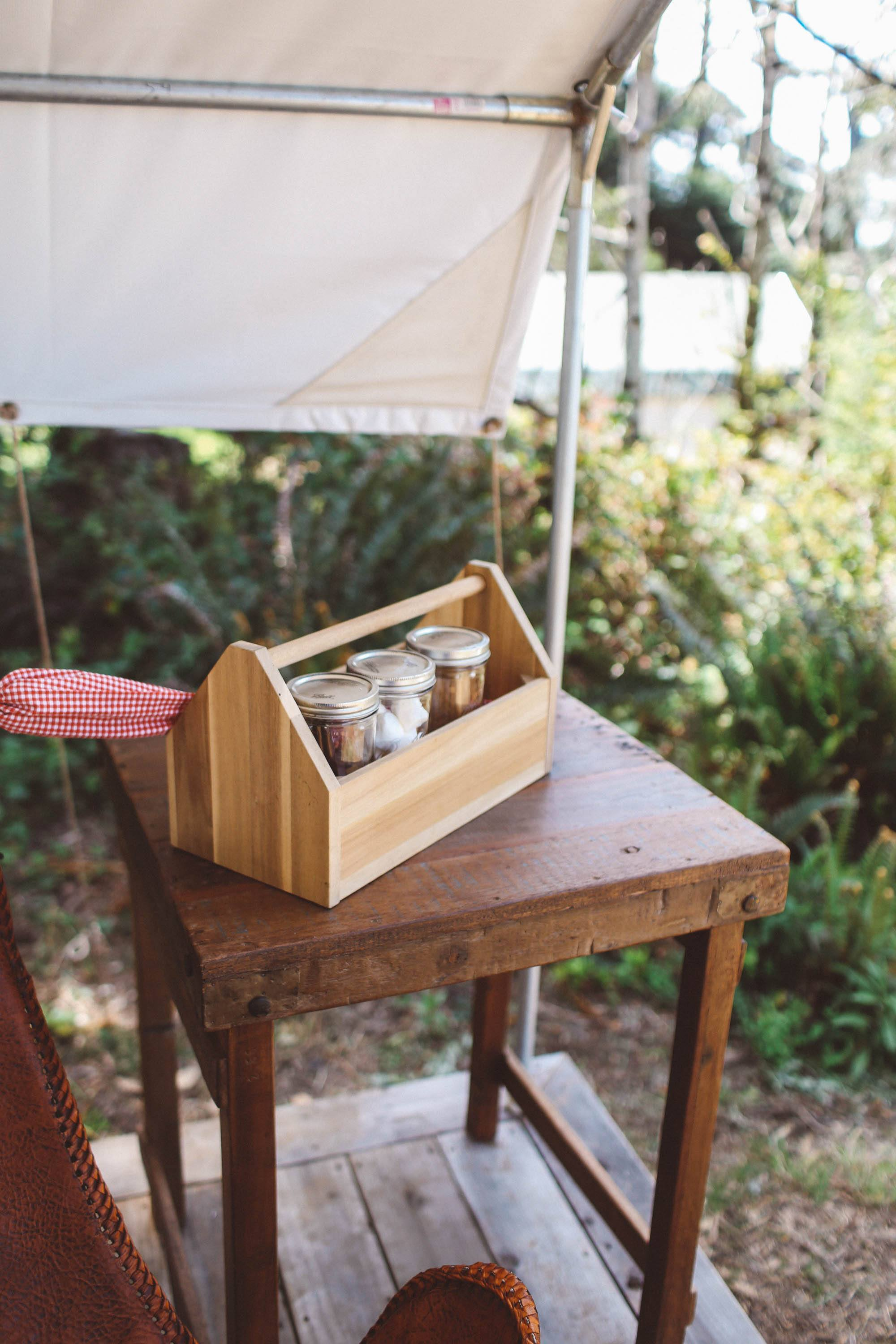 Wooden box with jars on a table on tent porch