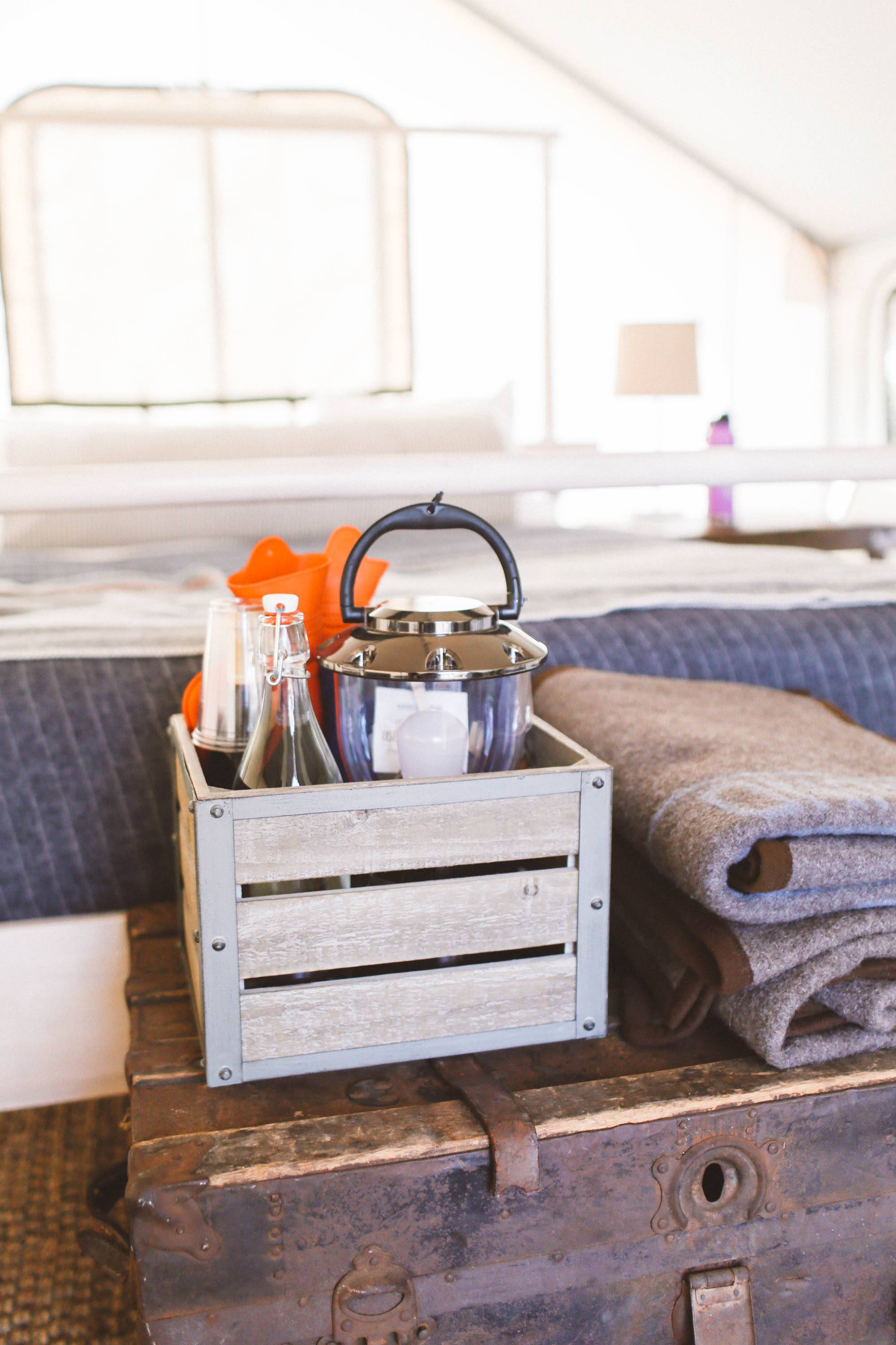 wooden crate with ammenities and towels sitting on wooden chest in tent