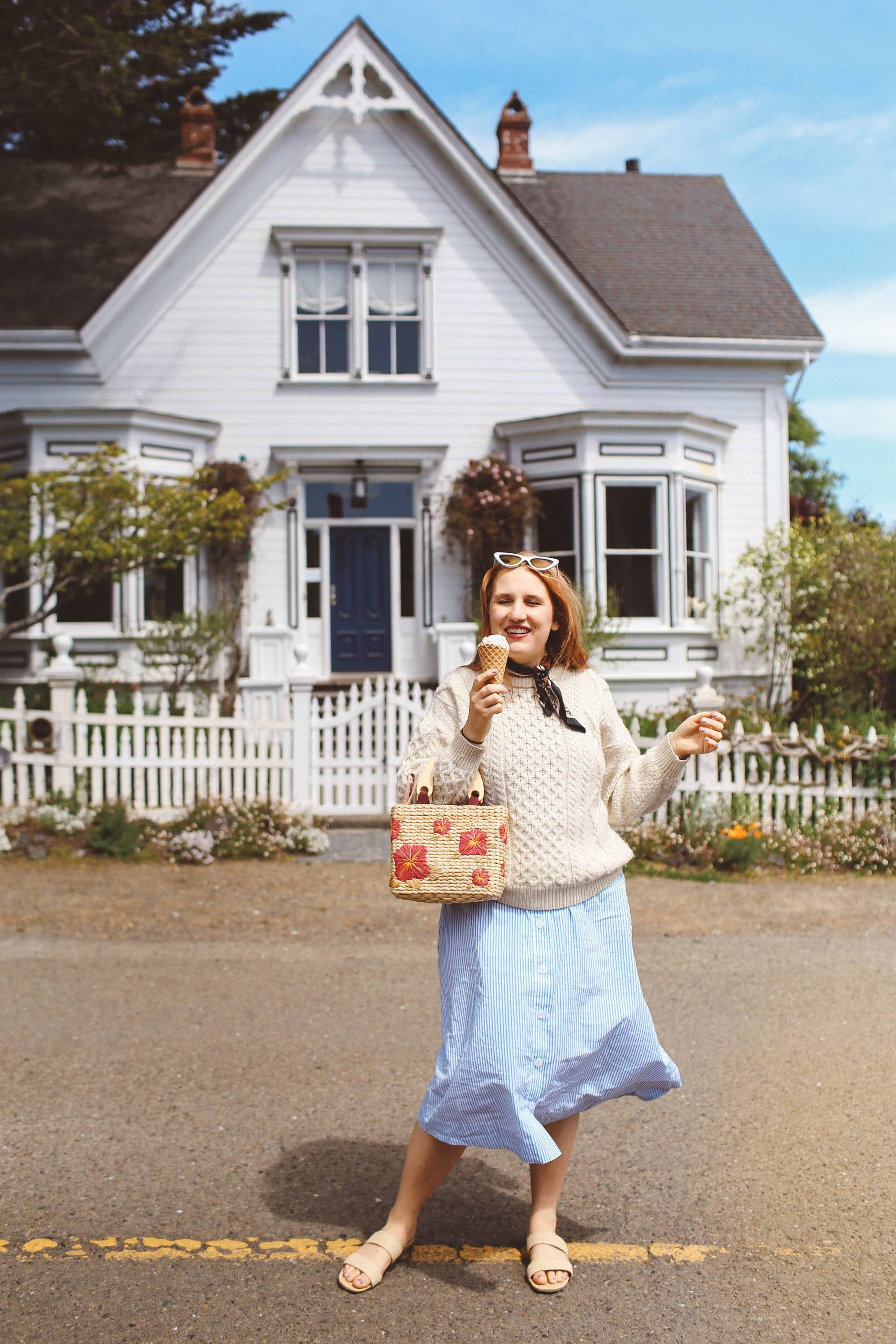 Woman in white wool sweater and flower straw bag eating ice cream