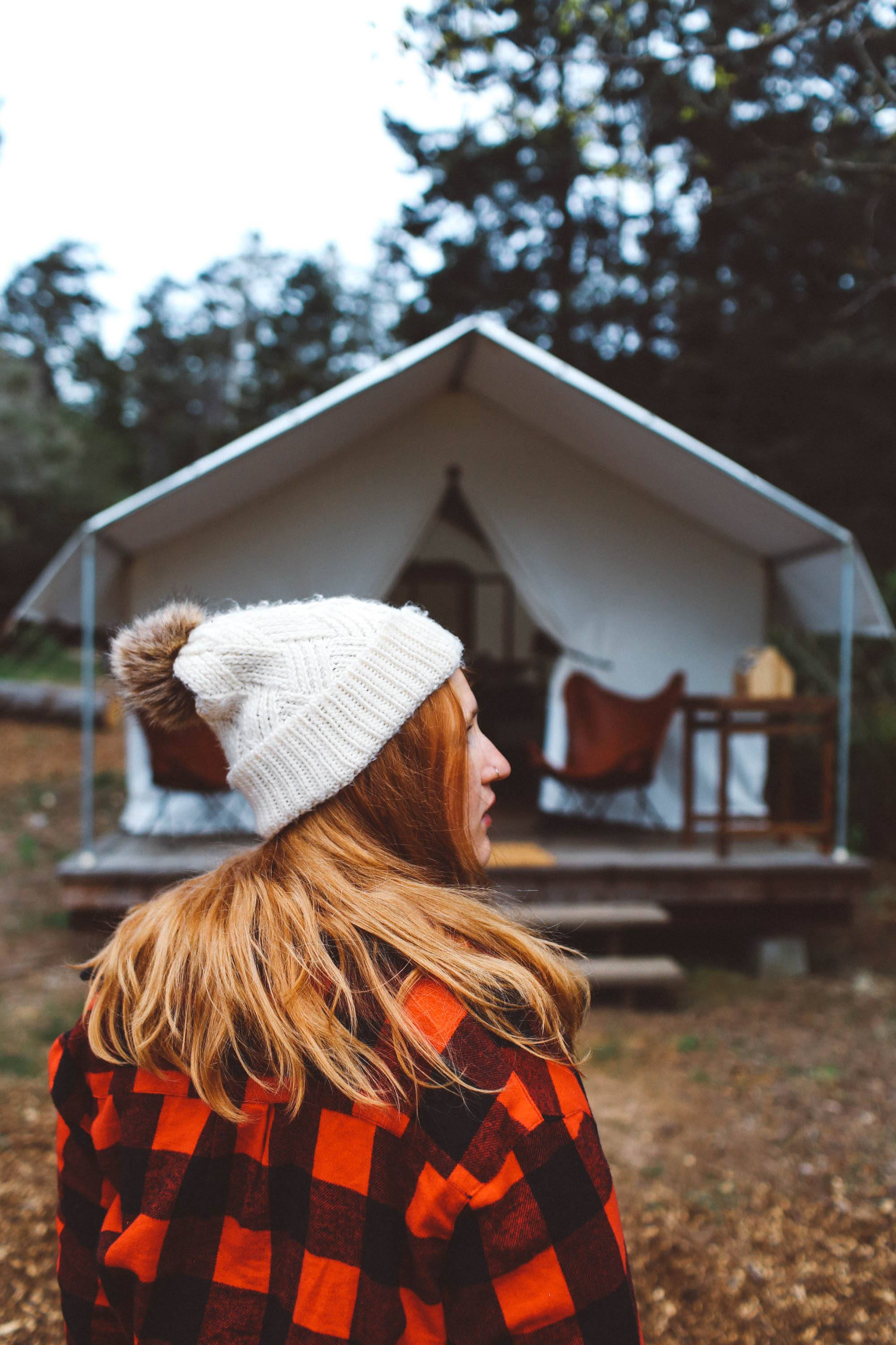 Woman wearing a plaid shirt and white puff beanie in front of tent