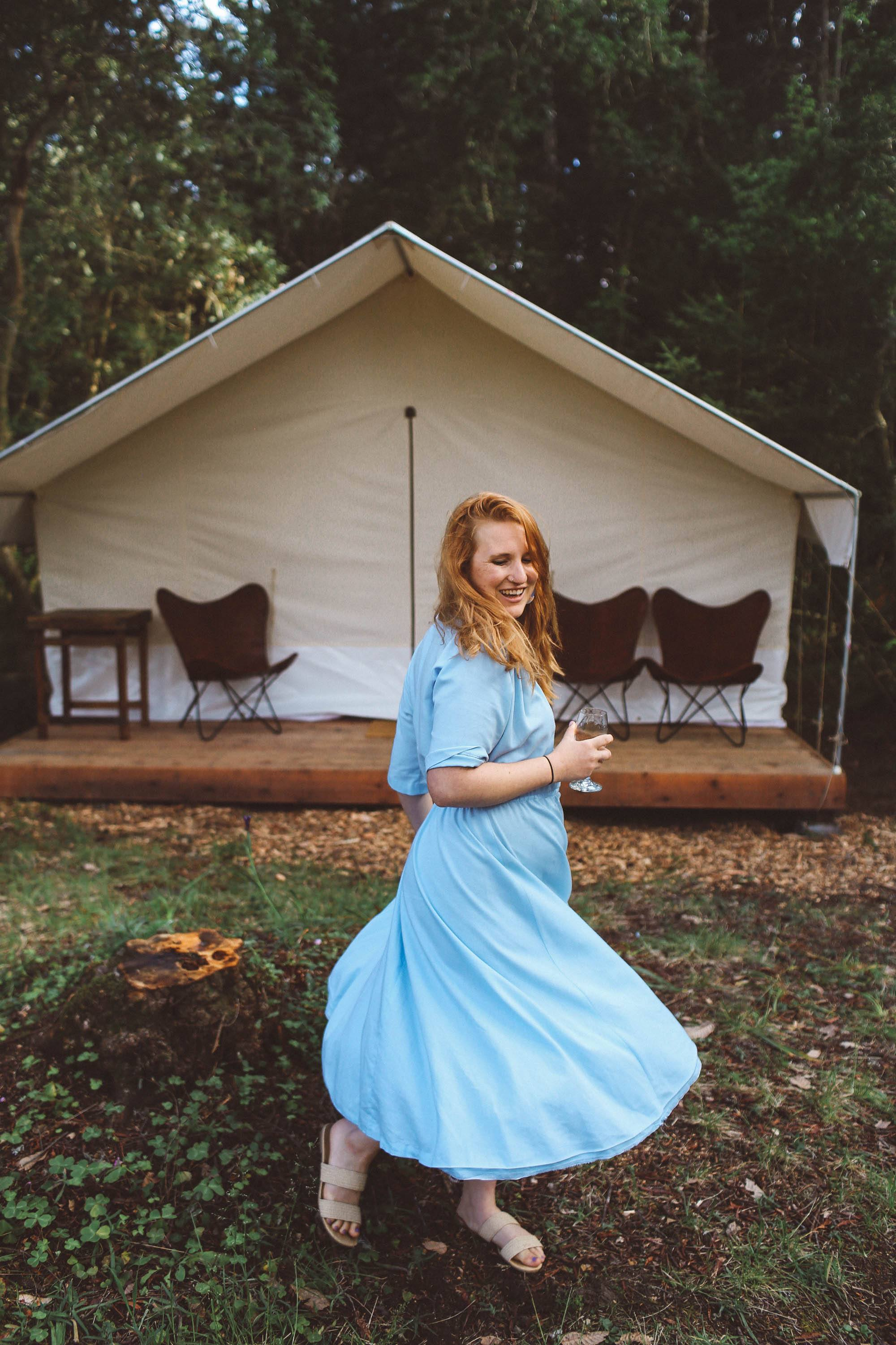 Woman wearing vintage light blue dress twirling in front of tent