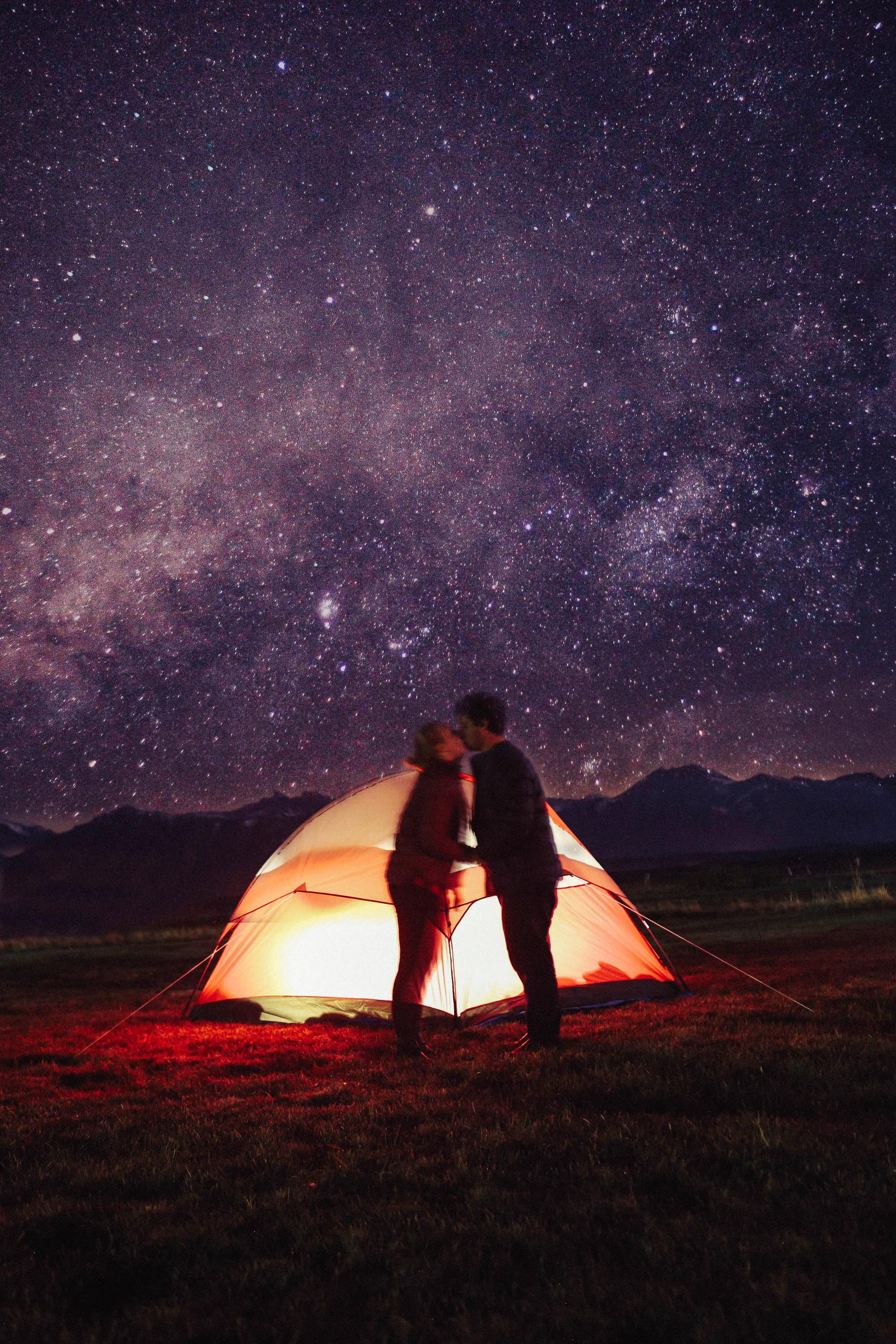 people kissing in front of a glowing tent on a starry night
