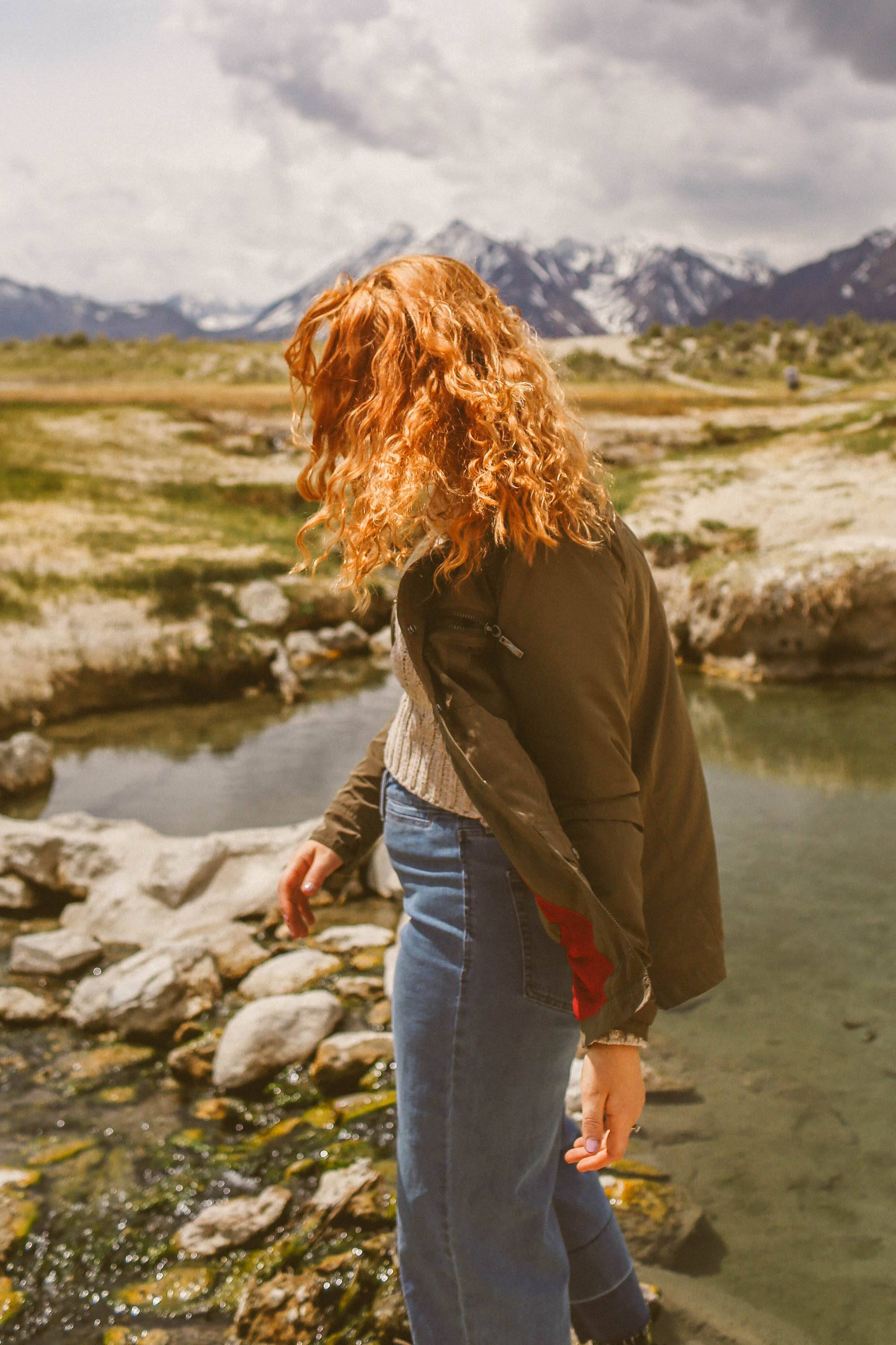 Woman in green MontanaCo jacket standing next to a hot spring in the mountains