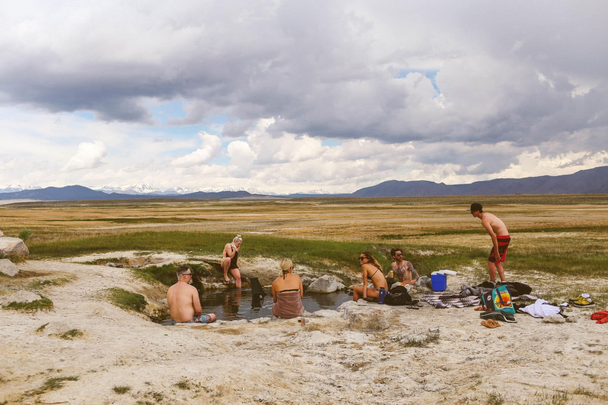 people sitting in a heart shaped hot spring in the mountains