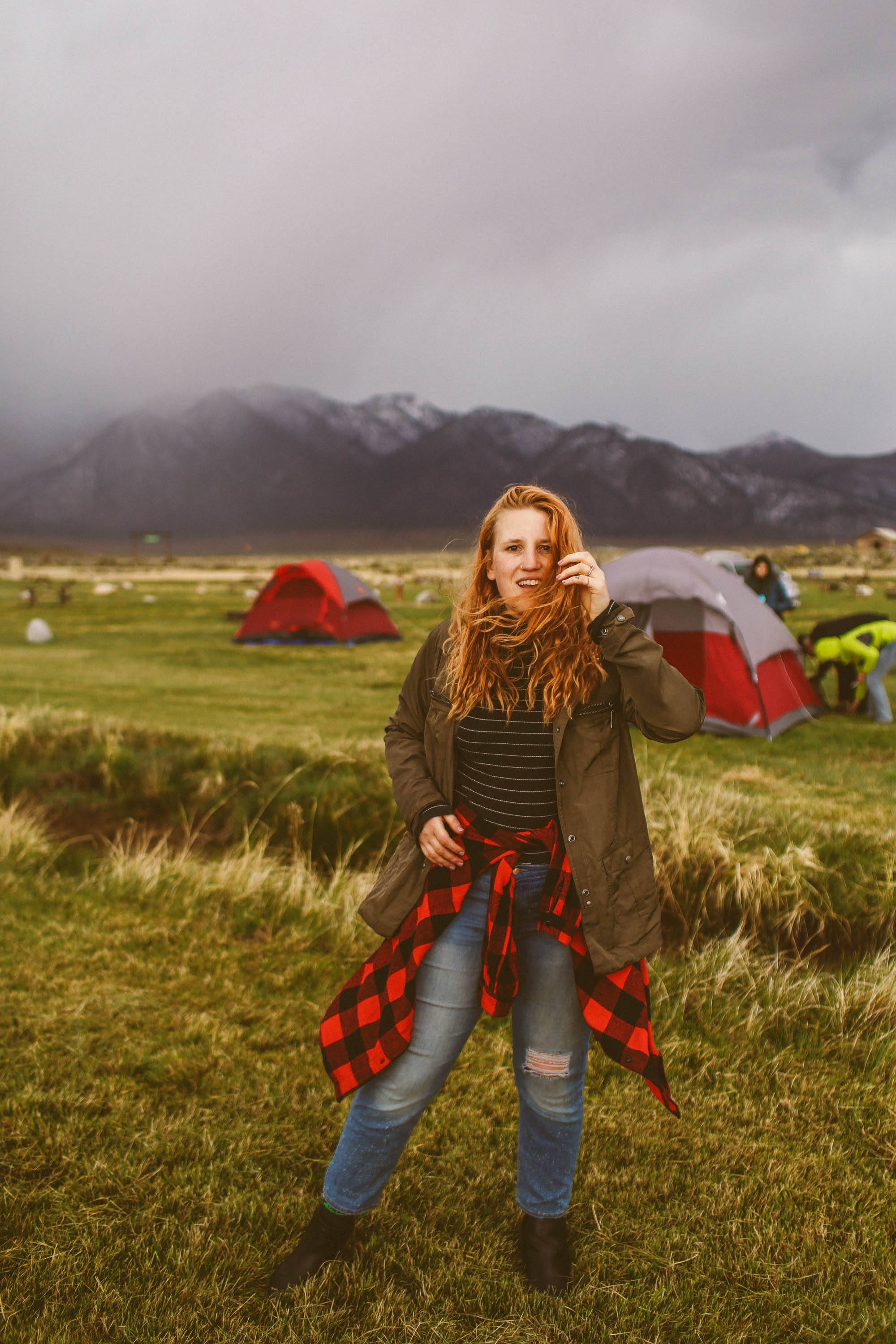 woman standing in the grass at a campground in the mountains