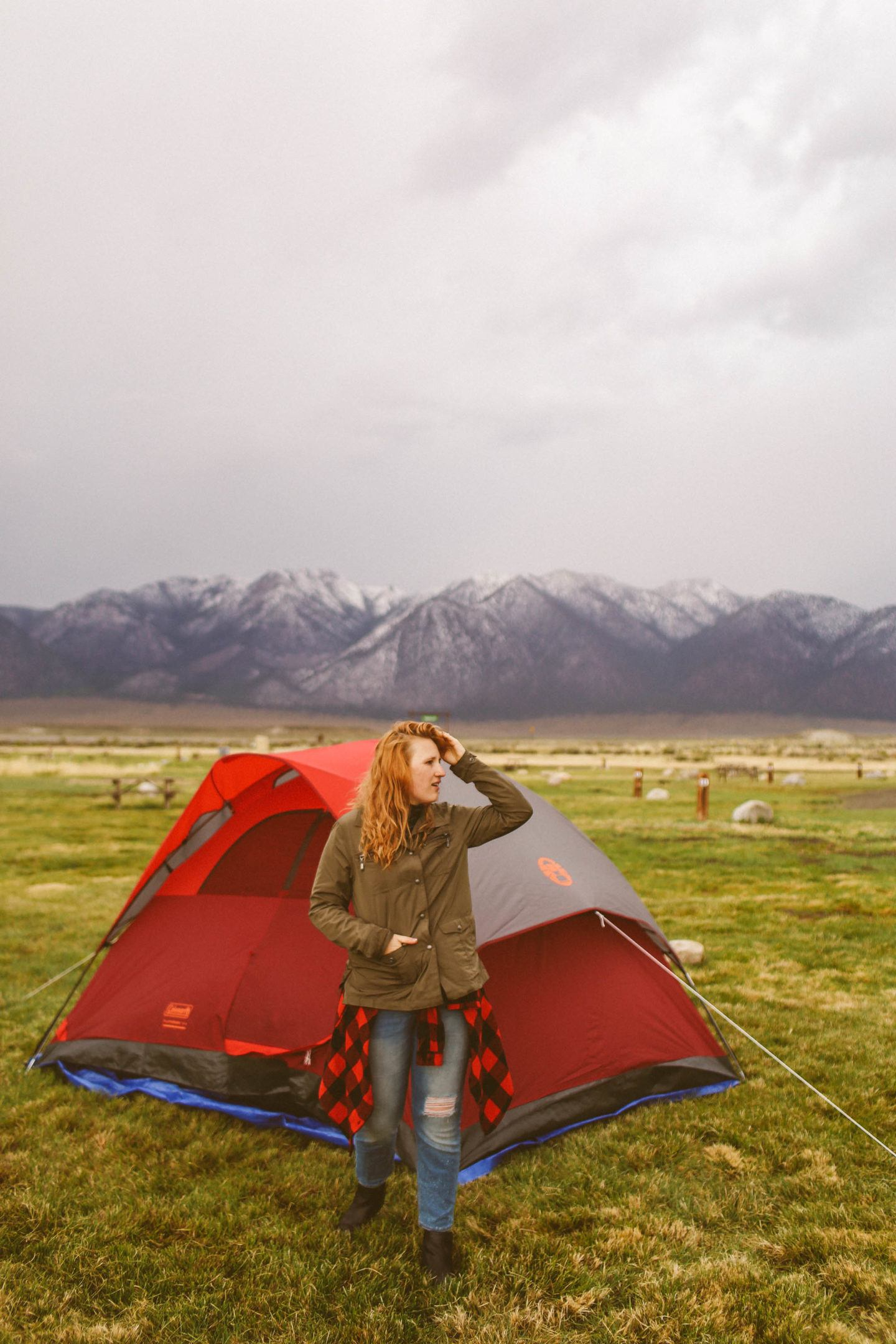 Woman standing in front of tent with mountains in the background