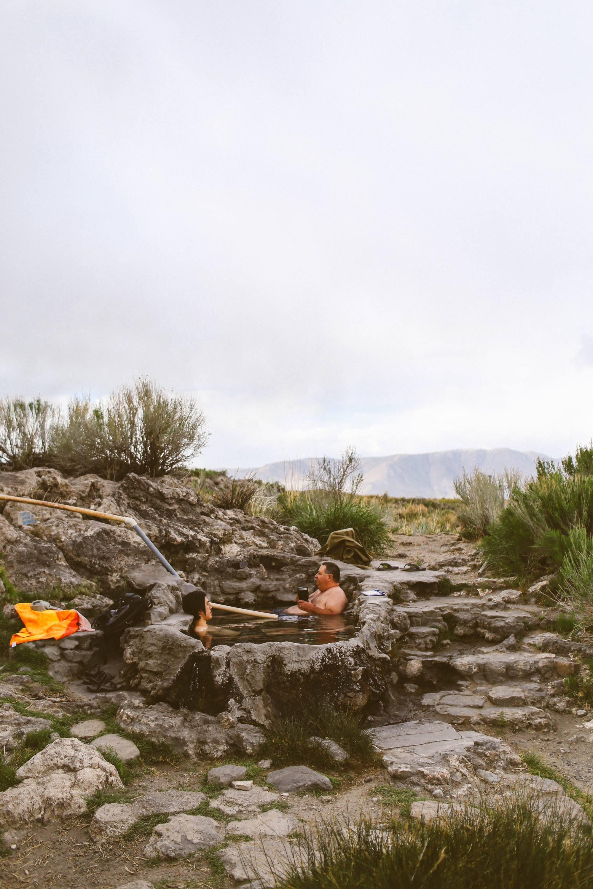 two people sitting in hot springs in the mountains
