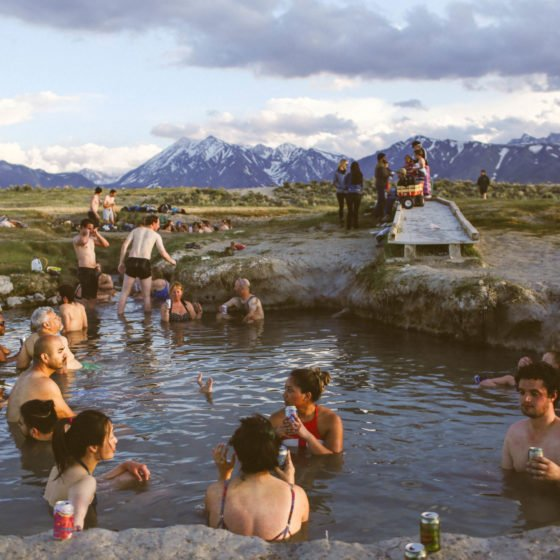 many people sitting in hot springs in the mountains