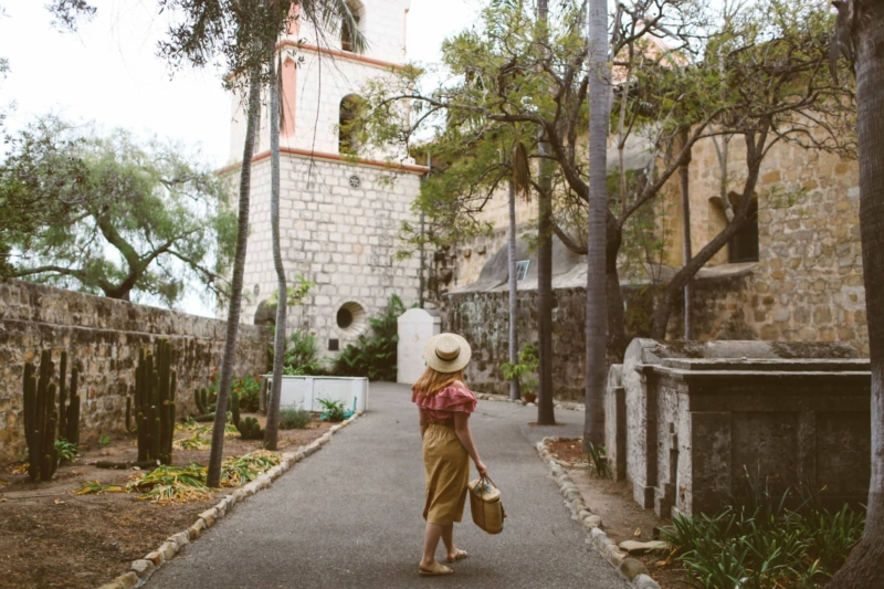 Woman wearing hat, red gingham top and a paper bag skirt at the Santa barbara mission