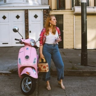 hand holding a Starbucks card next to a pink Vespa