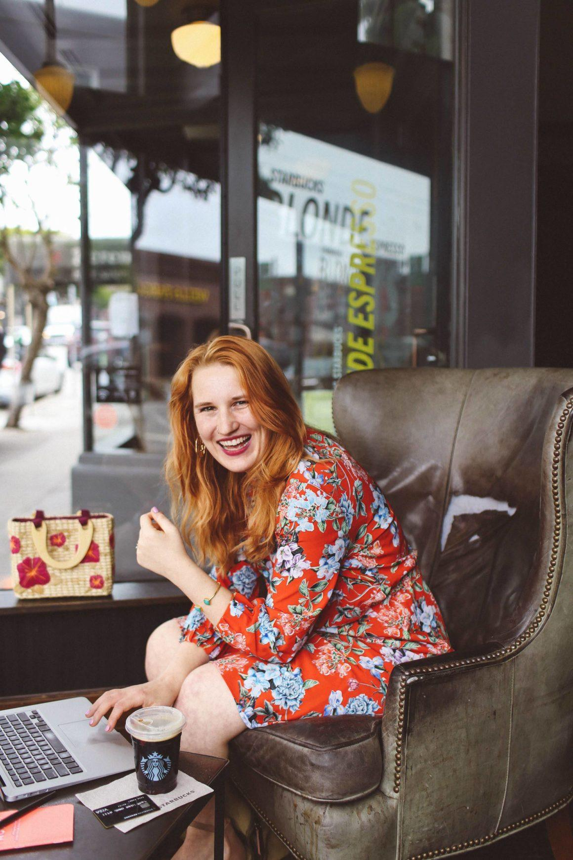 Woman in red floral dress working at Starbucks