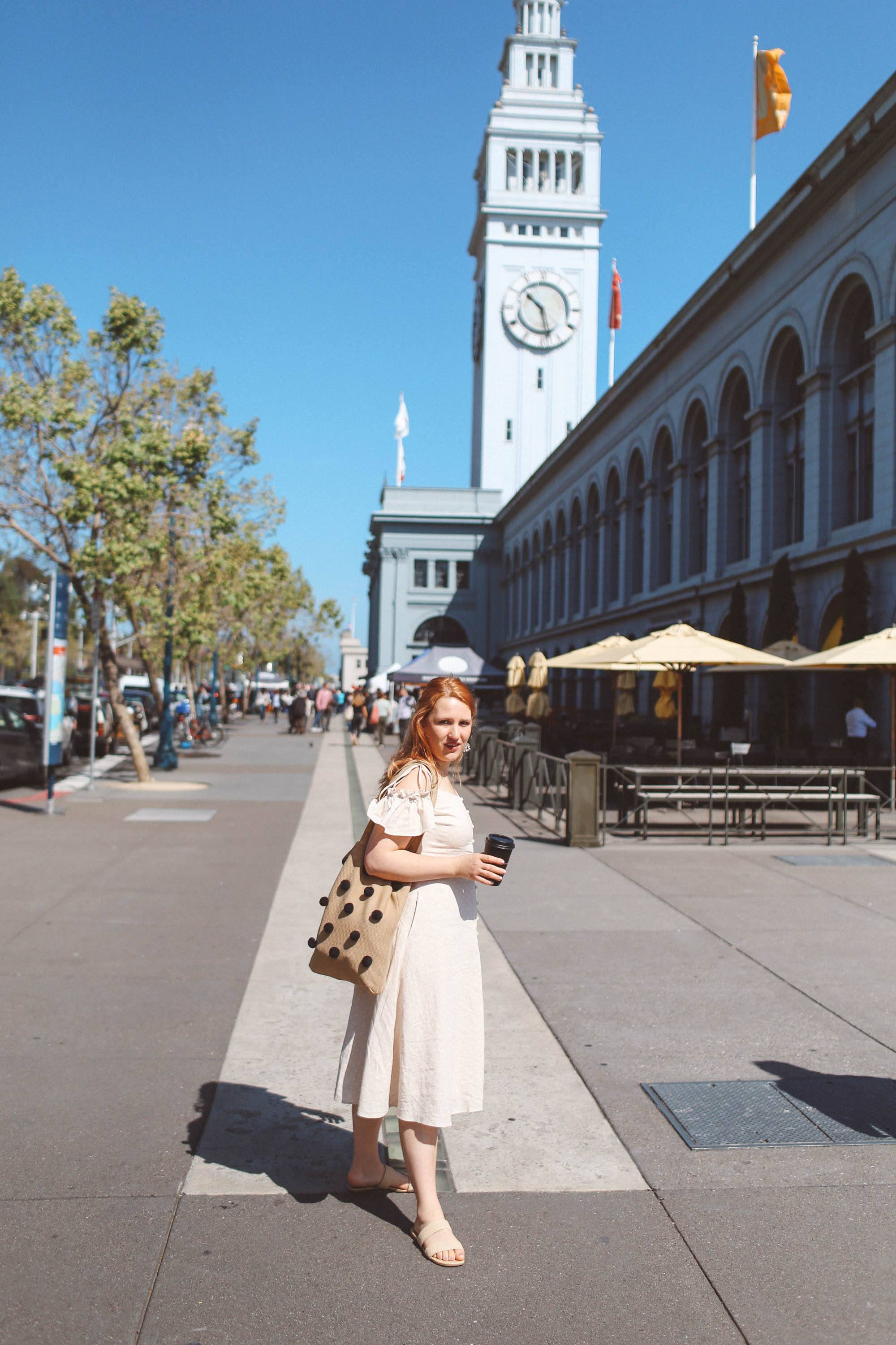 Woman wearing vintage dress holding coffee by ferry building
