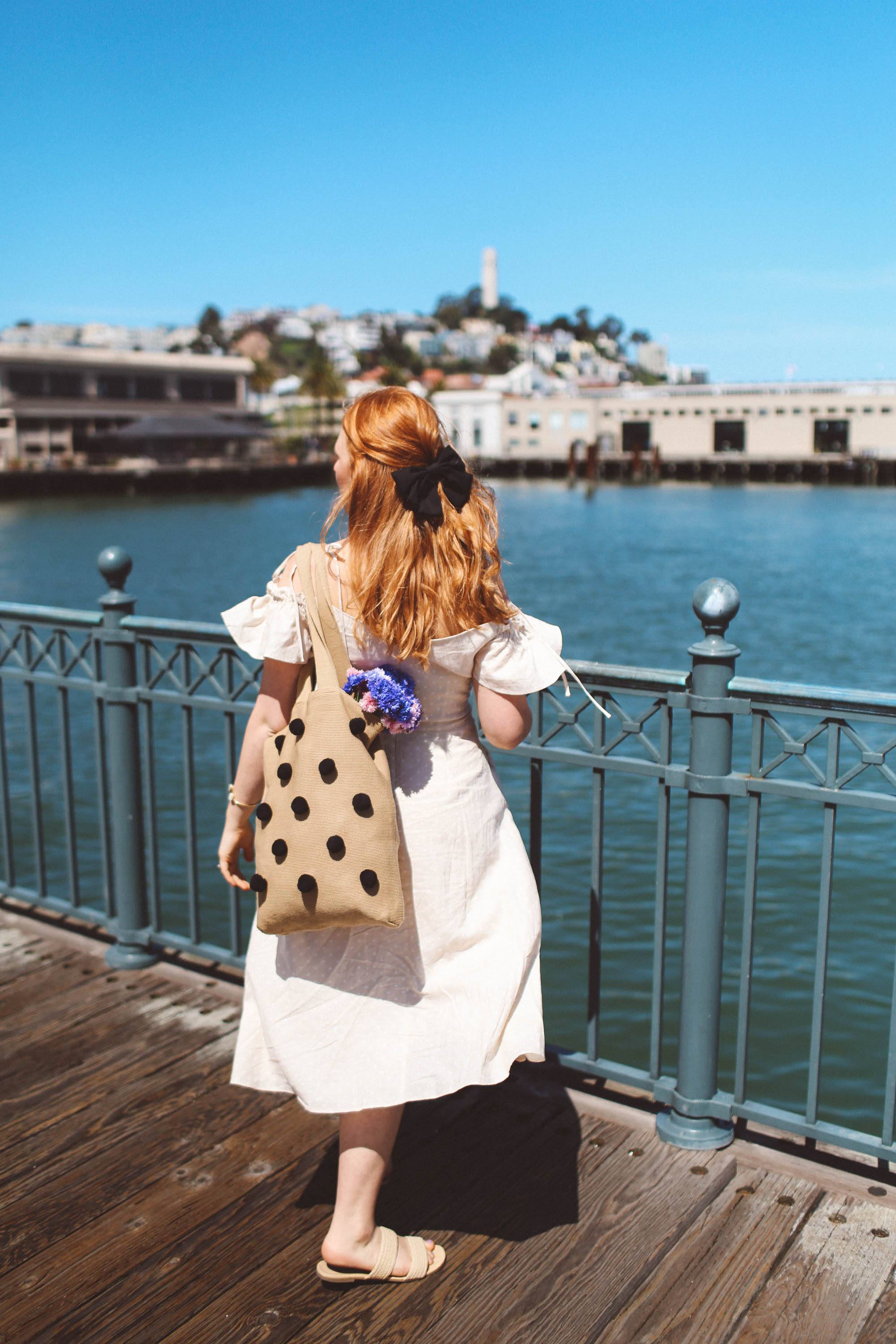 Woman in vintage dress with bag looking over the water