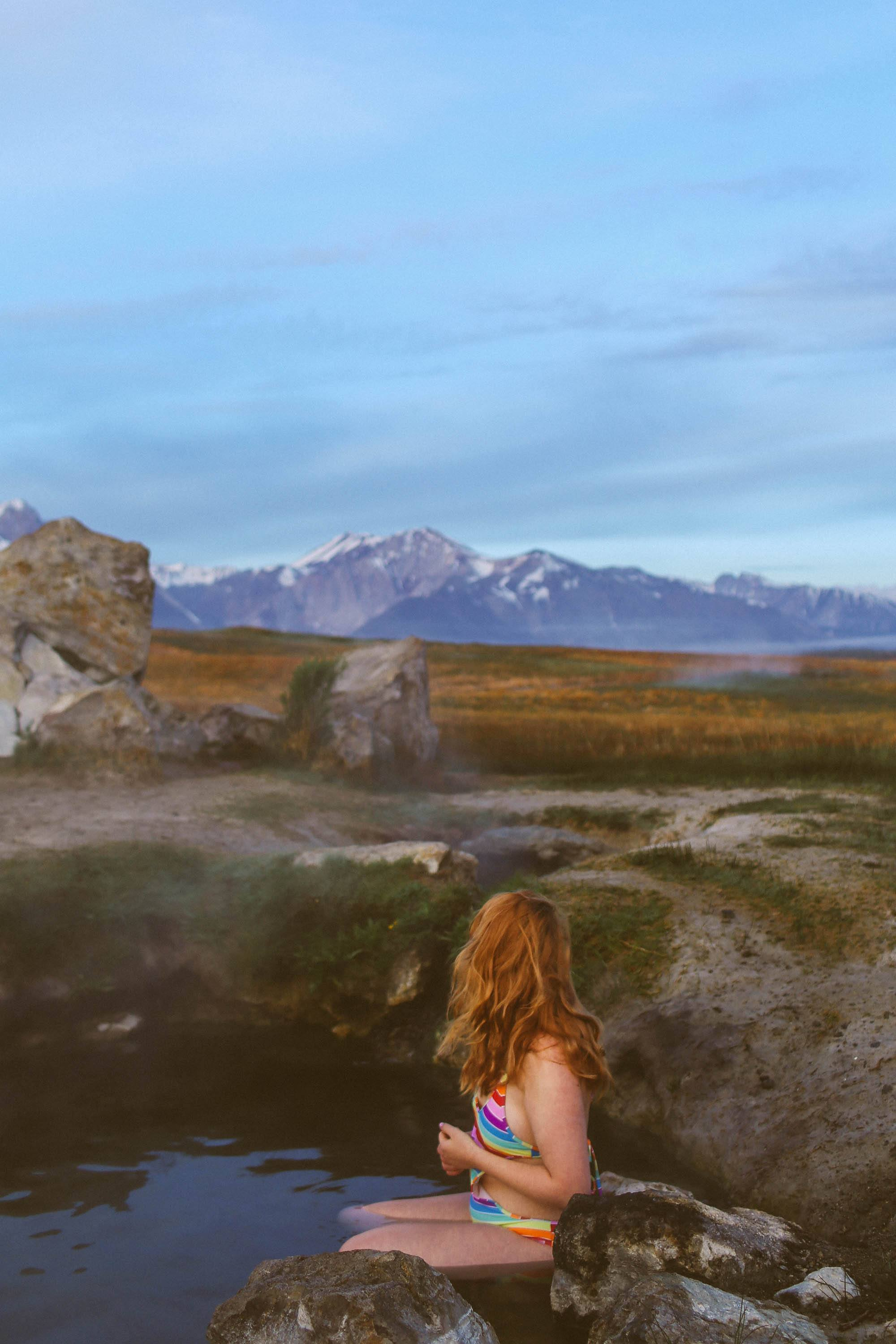 Woman in rainbow swimsuit sitting in a hot spring with mountains in the background