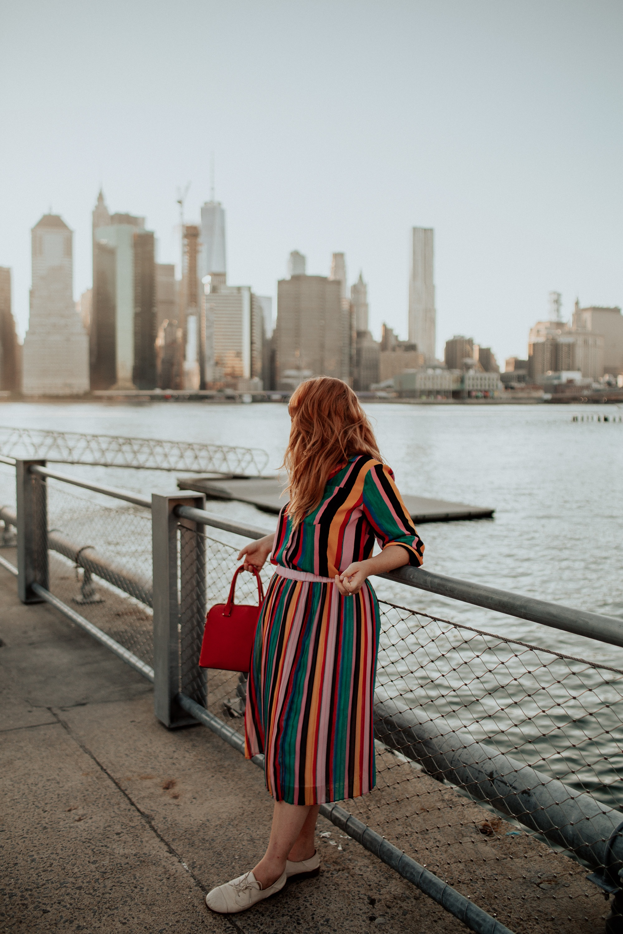 Woman in a Rainbow outfit looking at Manhattan from across the Hudson River.