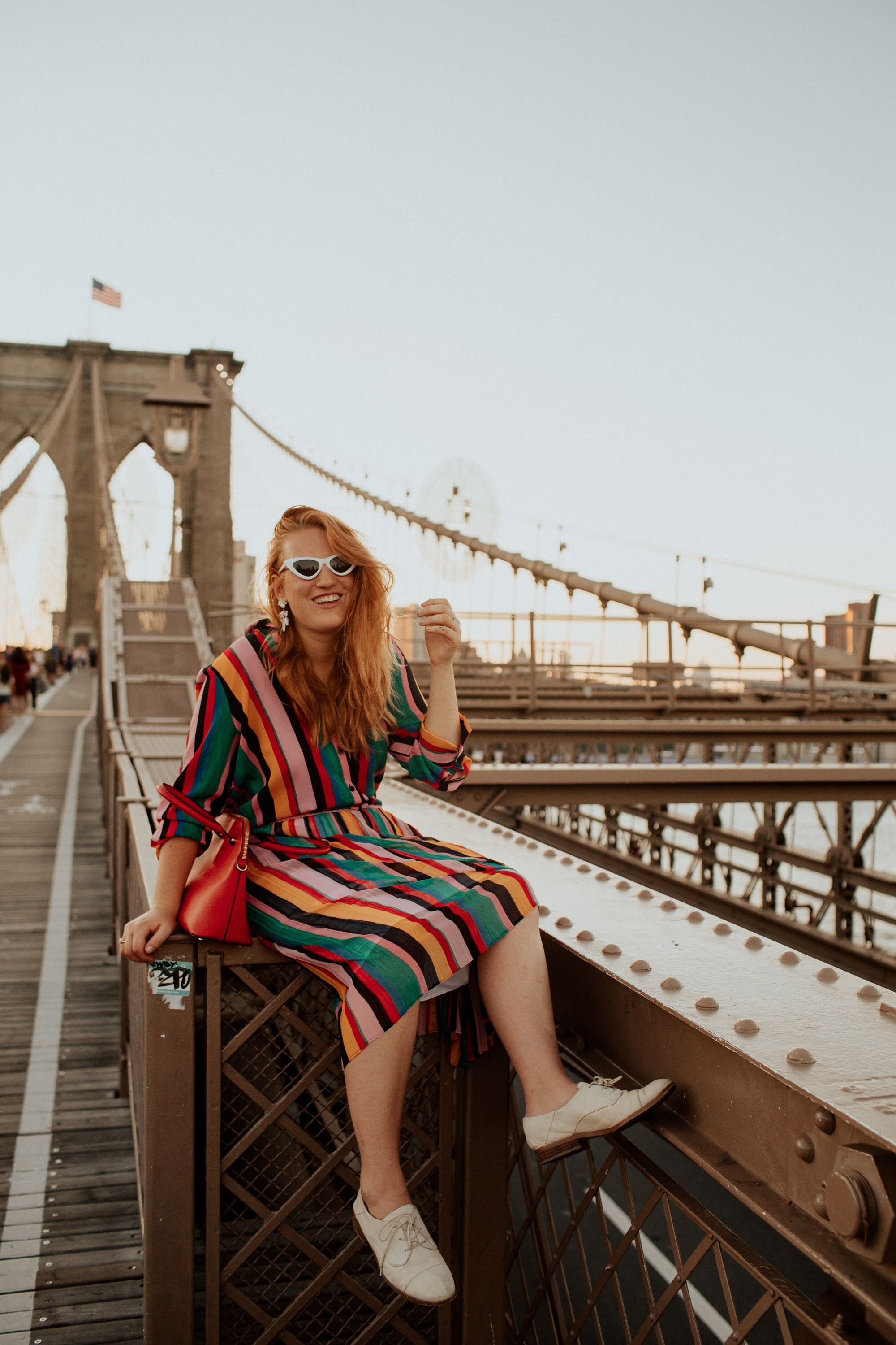 Woman in a rainbow Outfit sitting on the Brooklyn Bridge.