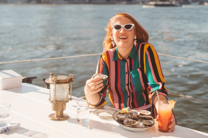 Woman in a rainbow outfit eating at a boat restaurant in Brooklyn