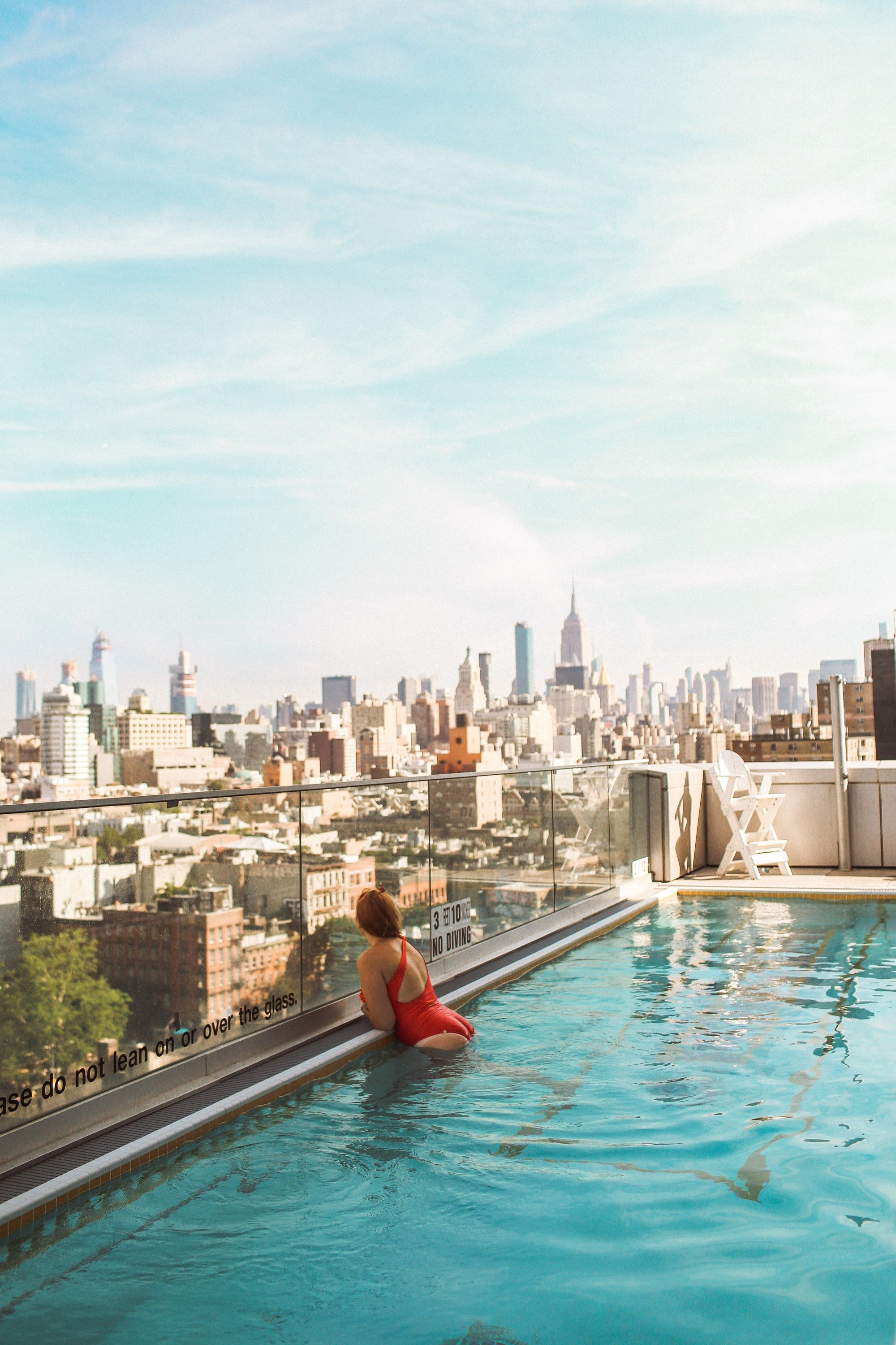 Woman looking out over Manhattan from a rooftop pool