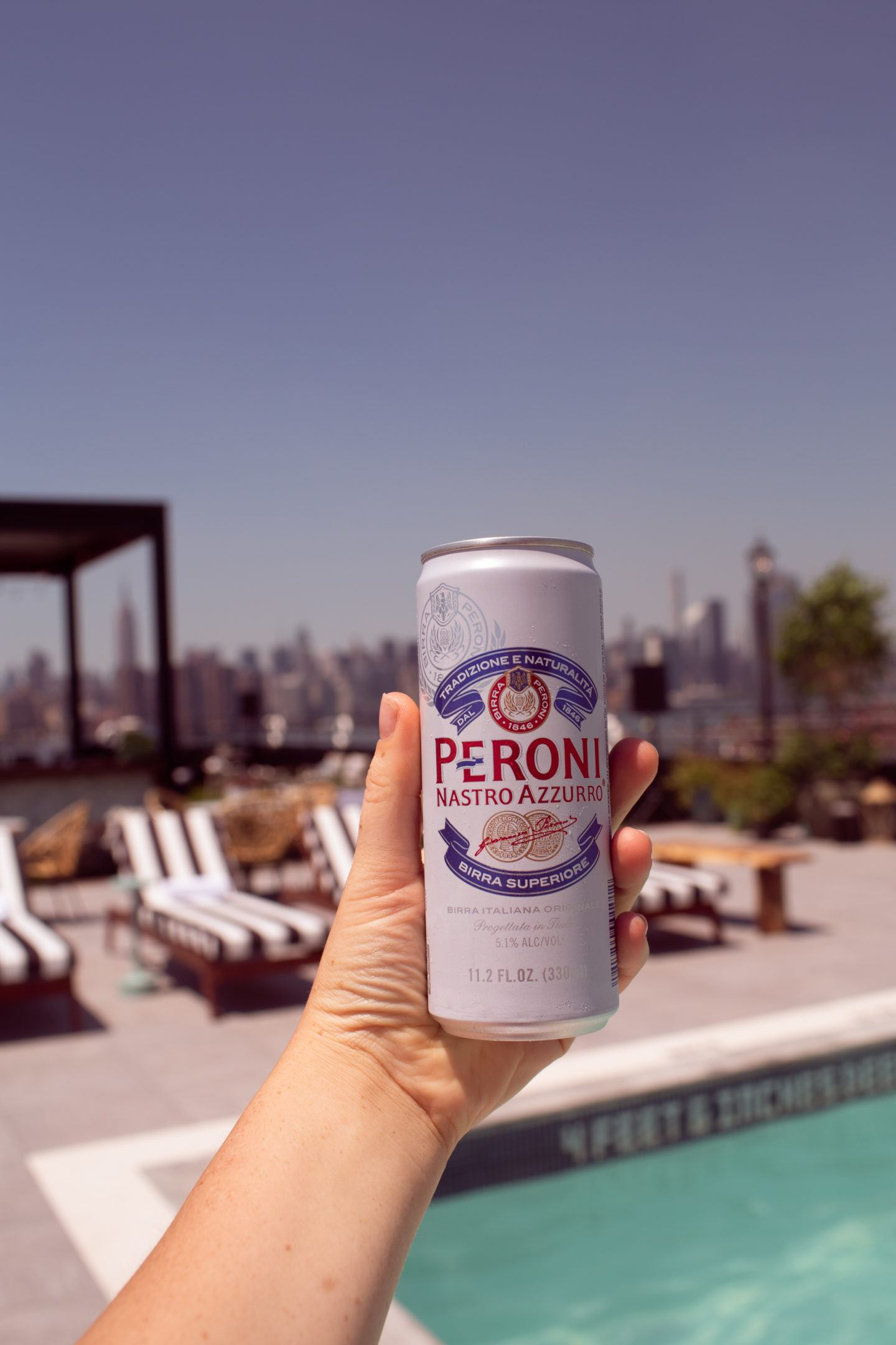 hand holding a beer at a rooftop pool in Brooklyn