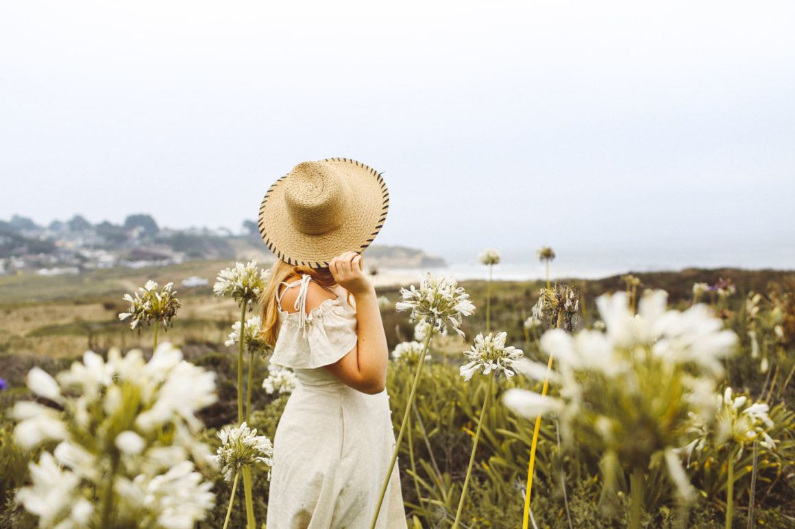 Woman in a dress and straw hat among the flowers