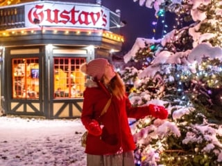 woman by christmas tree in front of gustav;s in leavenworth