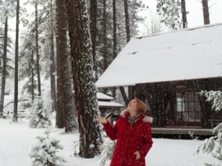 Woman in red coat at snowy Sleeping Lady Resort