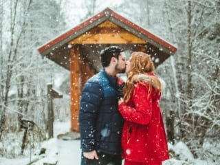 Man and Woman kissing in the snow at Sleeping Lady resort