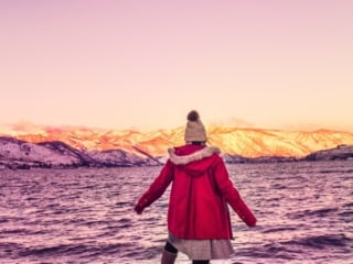 woman in red coat and beanie on lakeshore