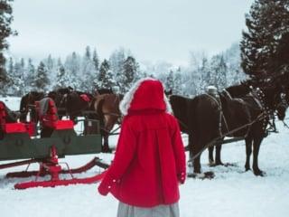 Woman in red coat walking towards sleigh