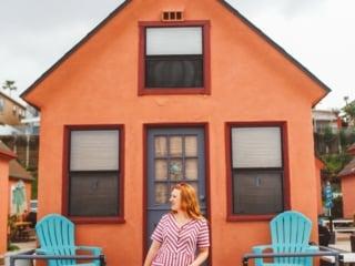 Woman standing in front of one of the Orange Beach rentals in Oceanside, Ca