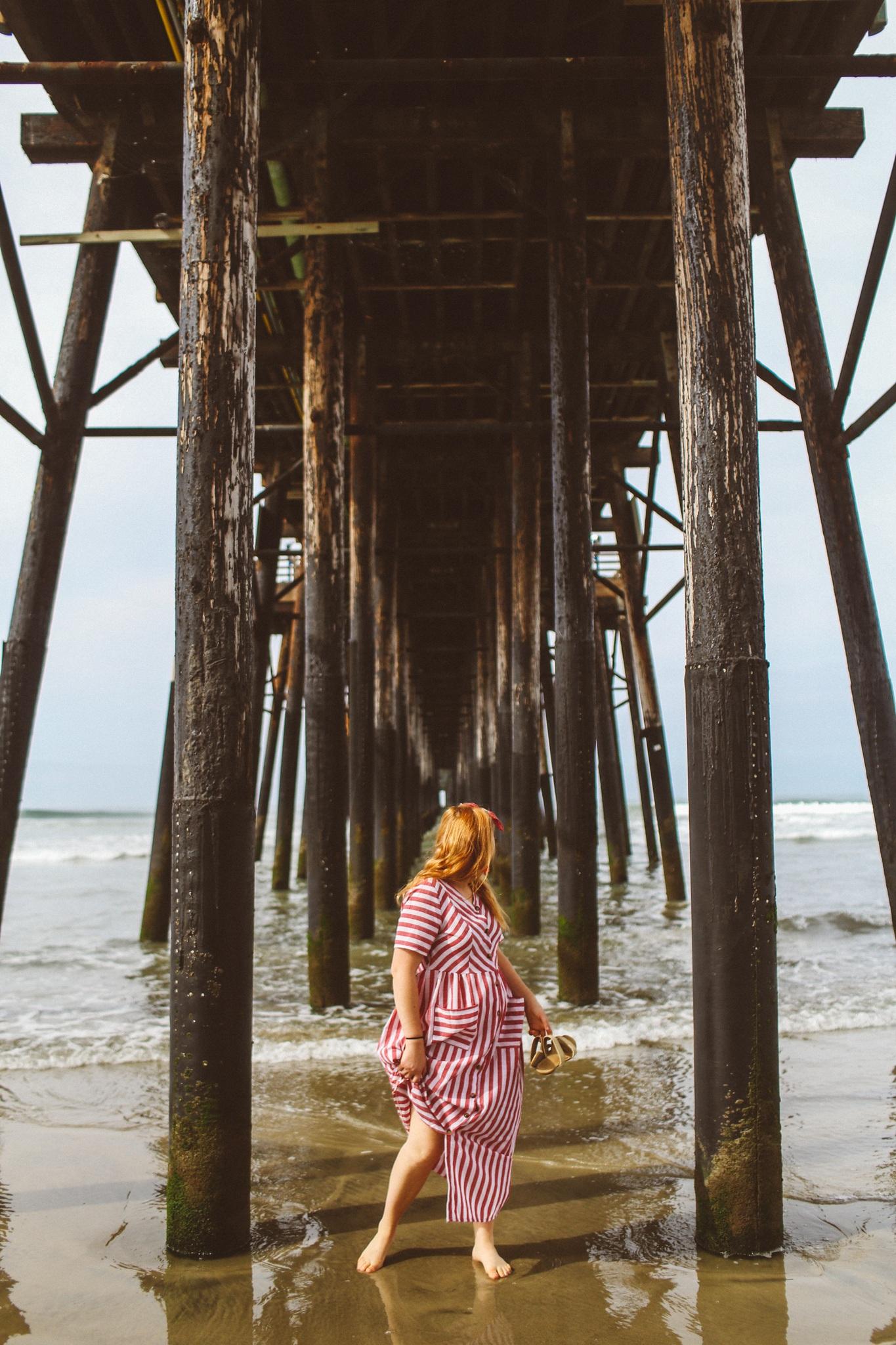 Walking on the beach underneath a pier in Oceanside, Ca
