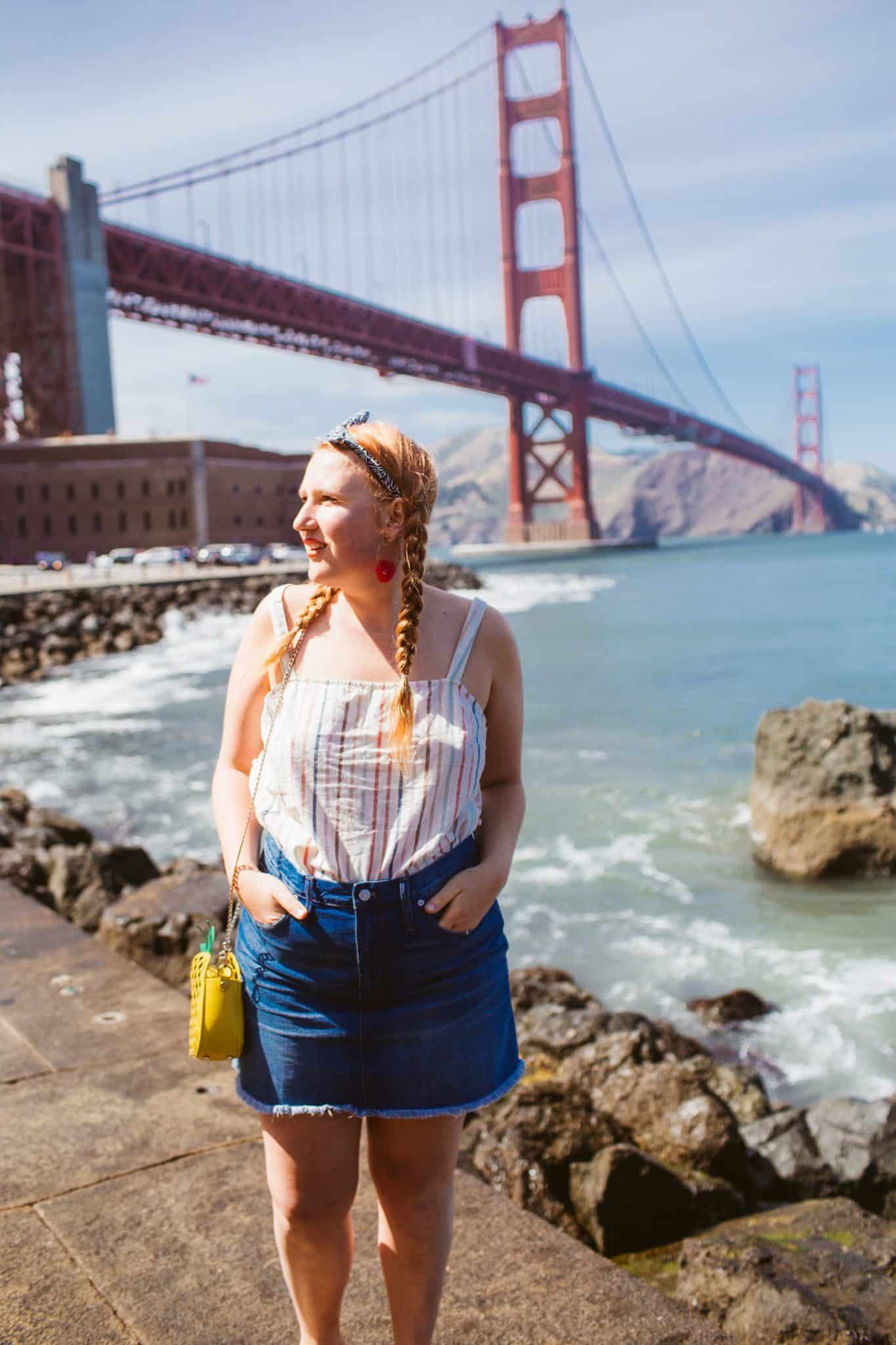 Woman in a denim skirt and a striped tank top at the Golden Gate Bridge in San Francisco