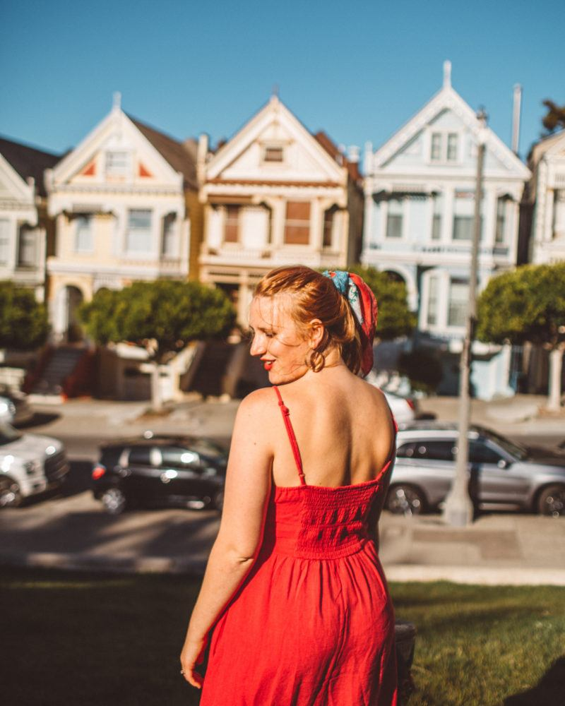 Kara of Whimsy Soul standing in front of the Painted Ladies in San Francisco wearing a red dress