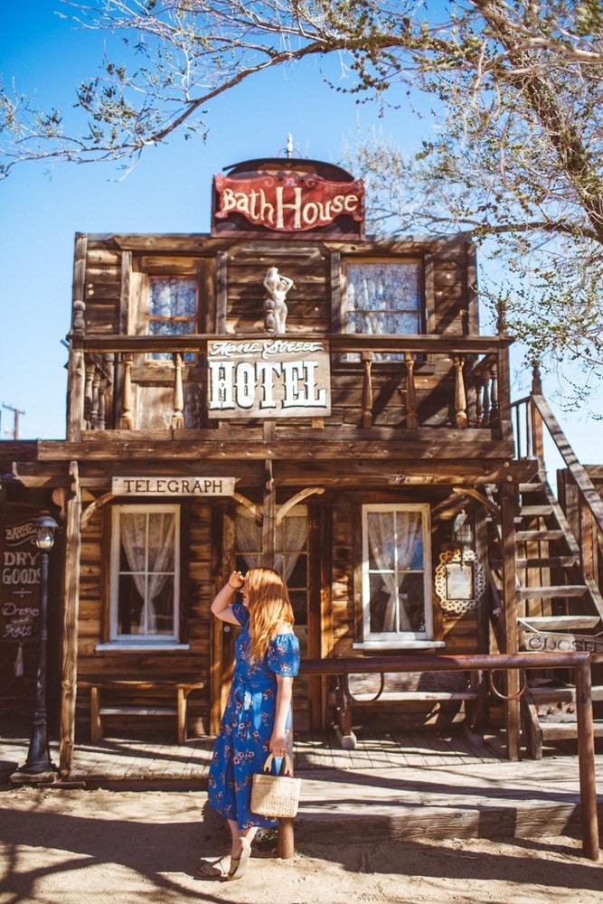 Kara standing in front of an old west hotel in Pioneertown, California