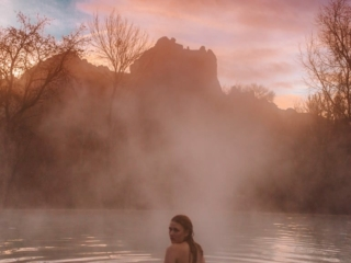 Kara of Whimsy Soul swimming in pool at sunrise next to Red Rocks at a Sedona Airbnb in Arizona