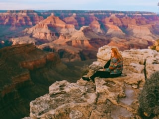 Kara of Whimsy Soul sitting on the edge of the Grand Canyon in Arizona